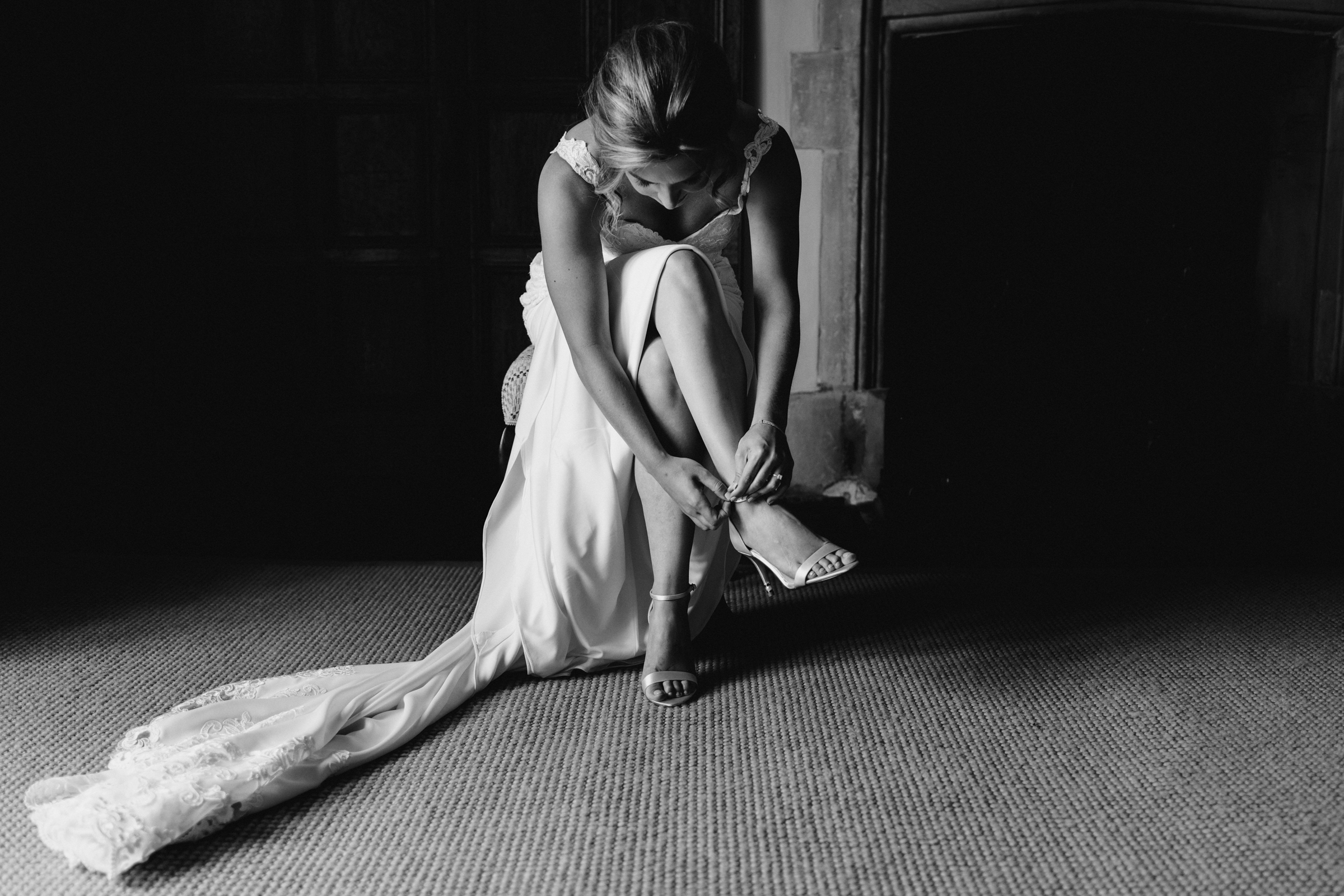 Bride putting on shoes - photo by MIKI Studios