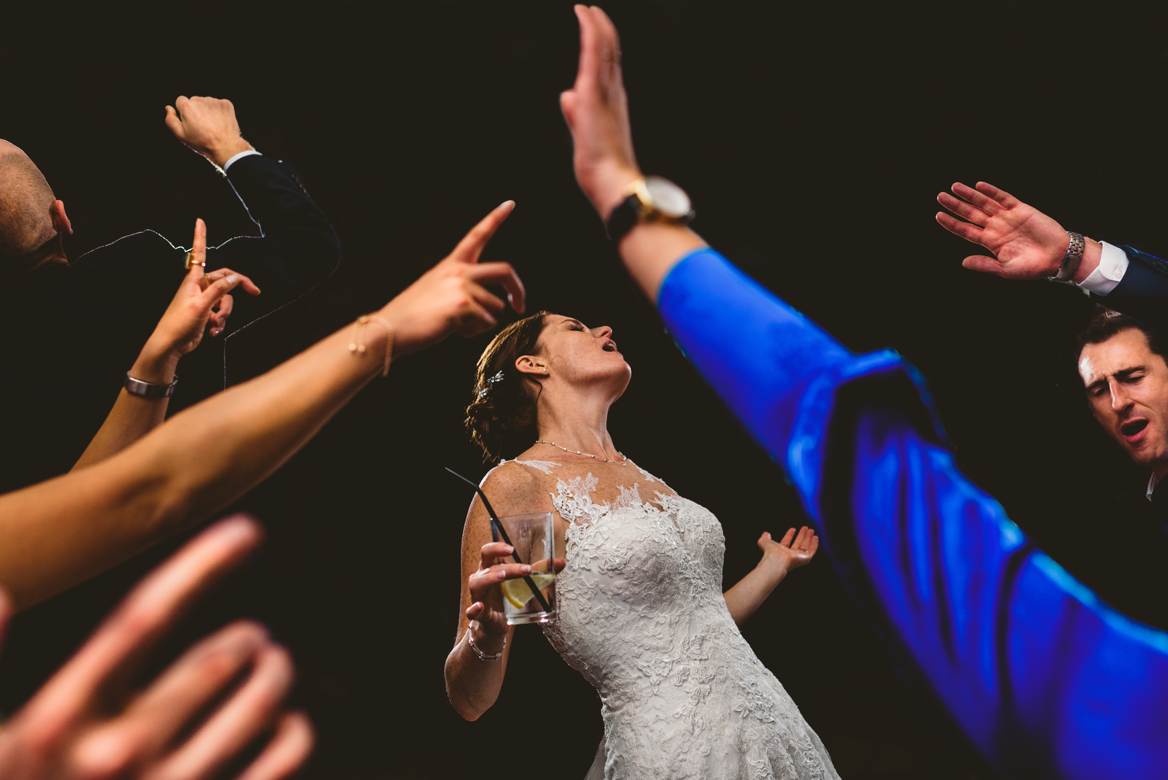 Bride sings surrounded by friends with hands in the air - photo by MIKI Studios