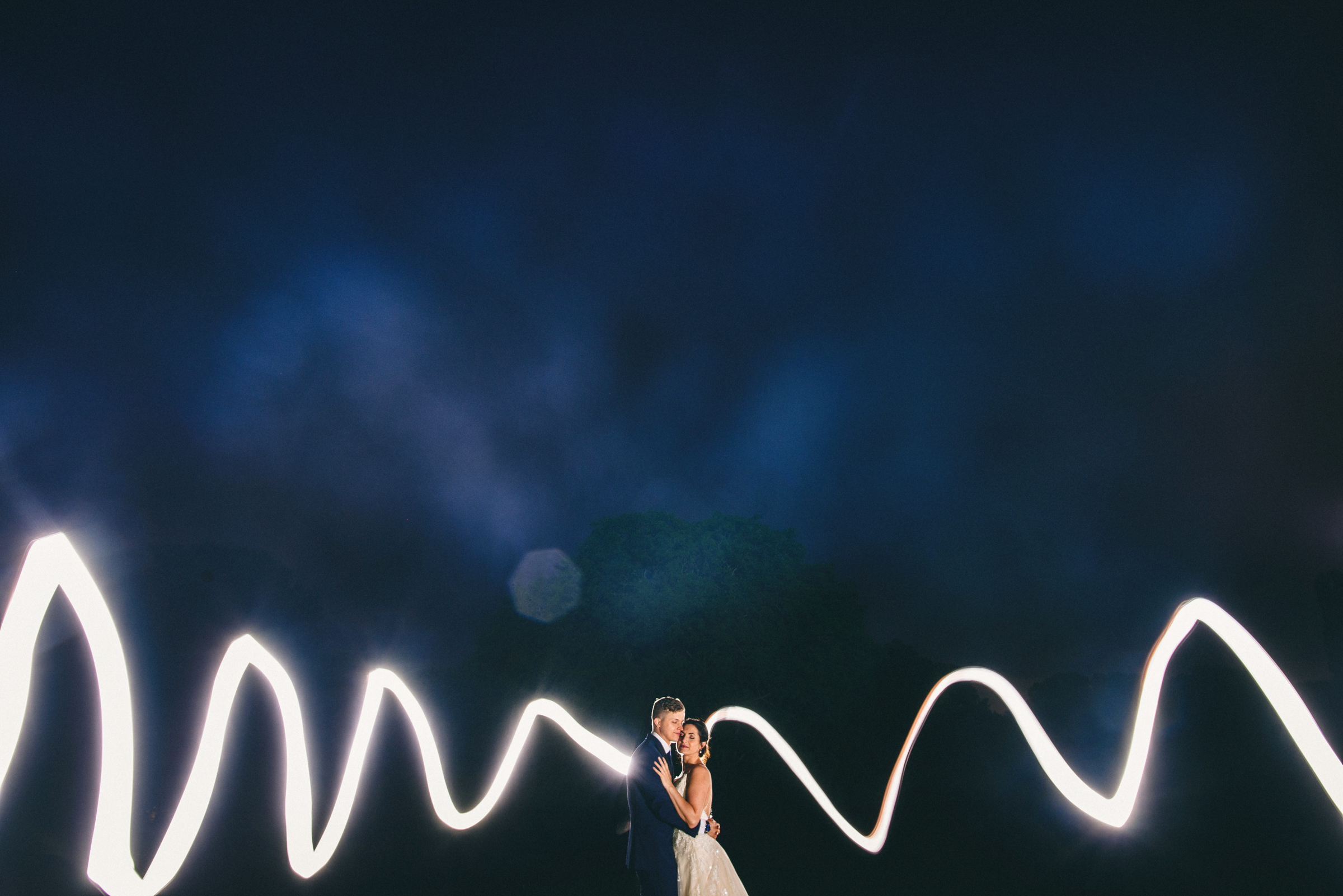 Couple landscape portrait with zigzag of white light - photo by MIKI Studios