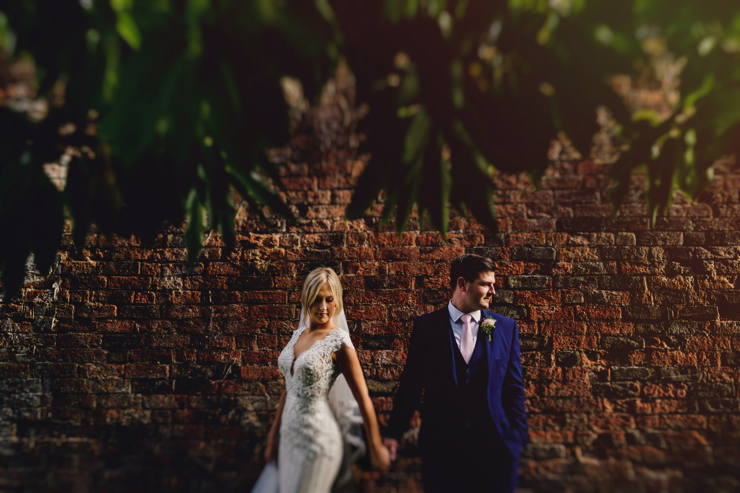 Couple portrait against brick wall and foliage - photo by MIKI Studios