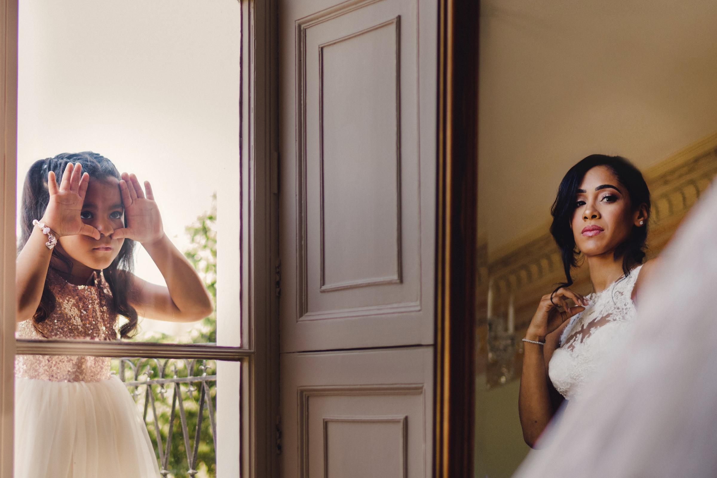 Flower girl peering in glass door at bride - photo by MIKI Studios