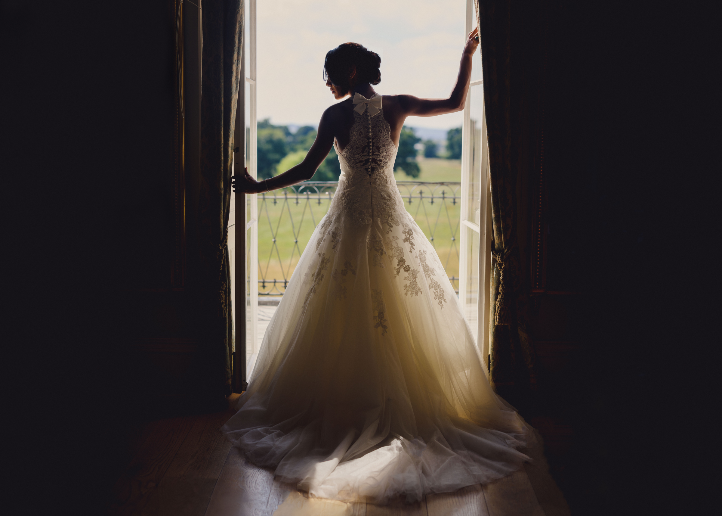 Glamorous bride looking out at balcony - photo by MIKI Studios