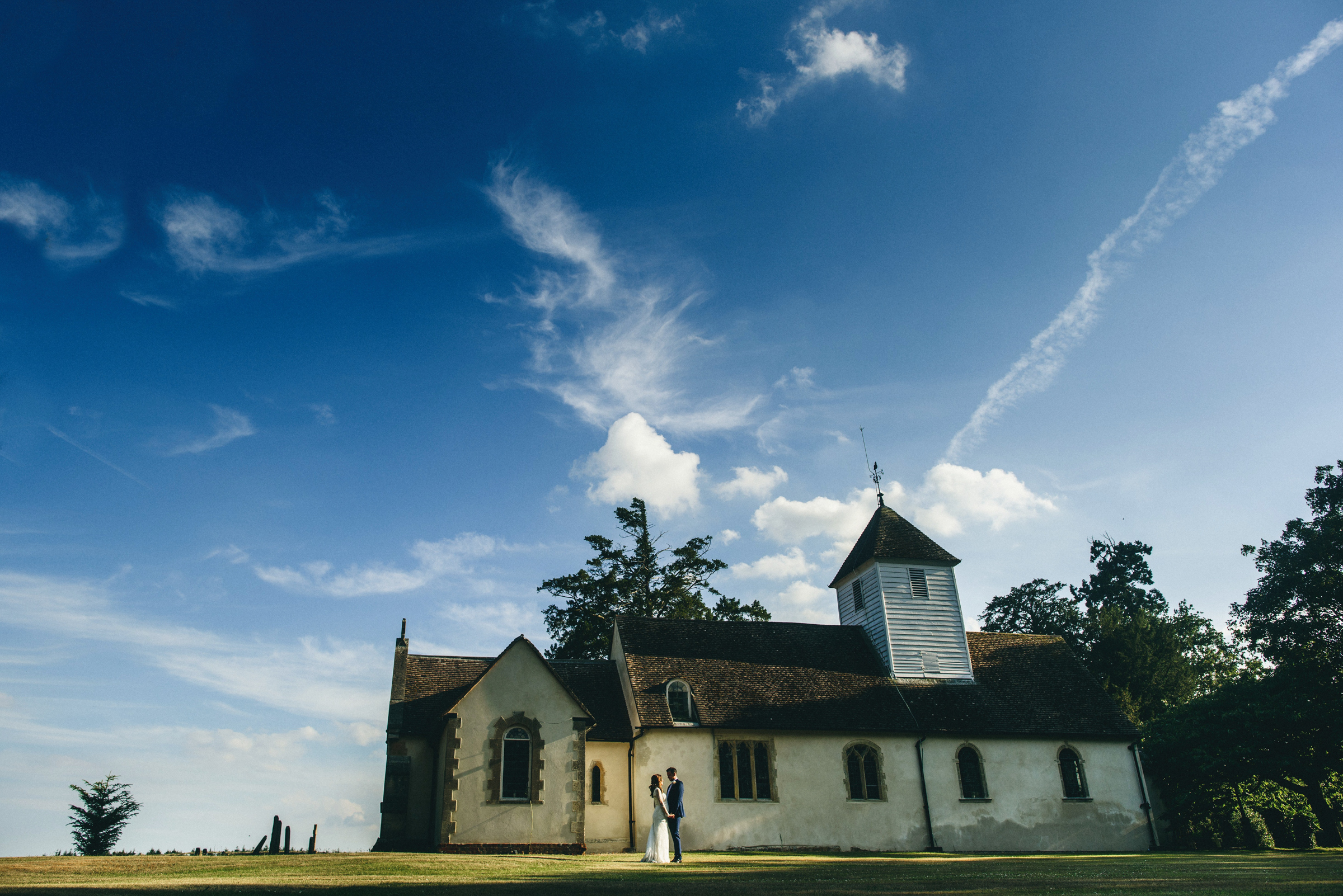 Landscape couple outside ancient country church - photo by MIKI Studios