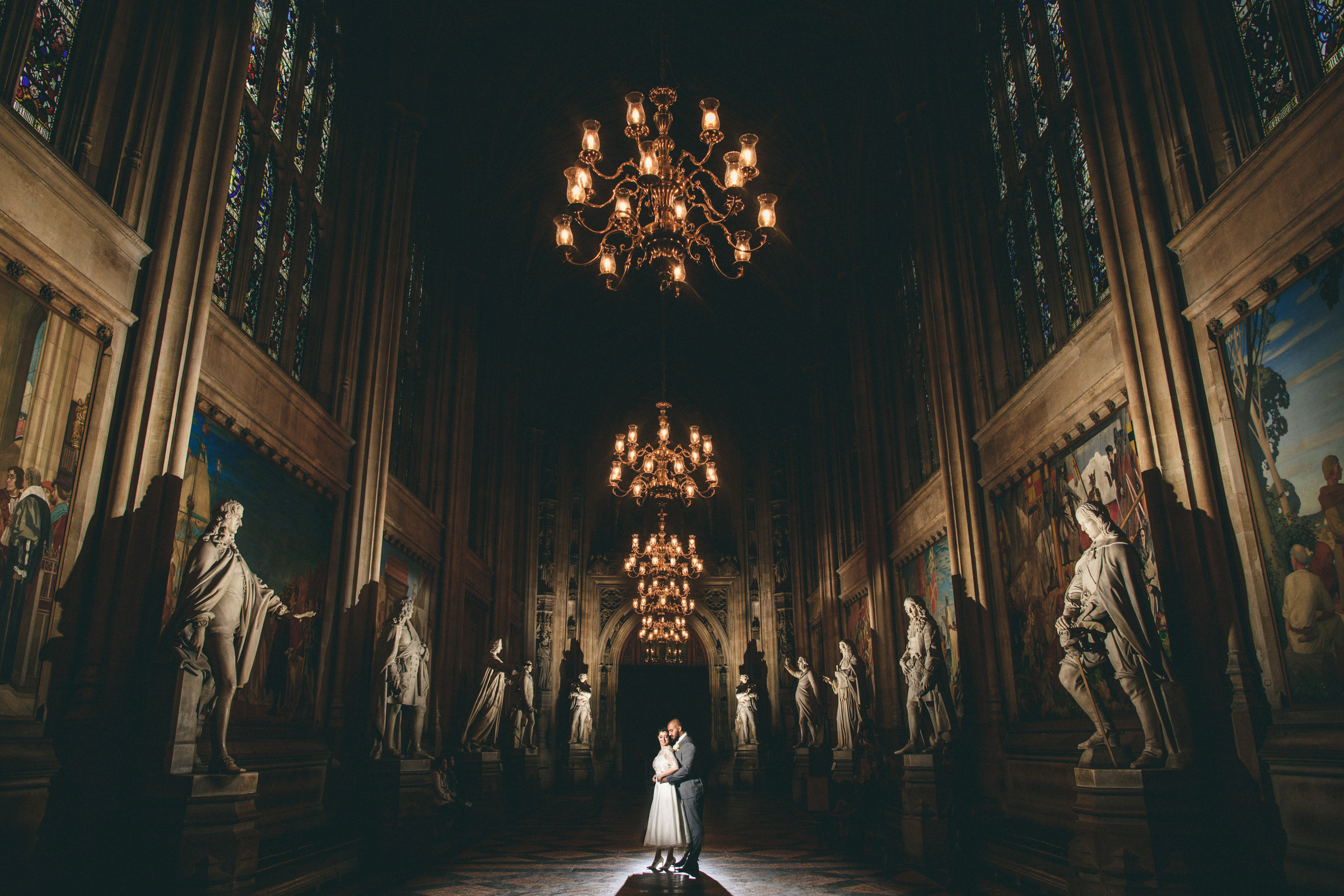 Low light couple portrait in museum setting with sculptures and chandeliers - photo by MIKI Studios