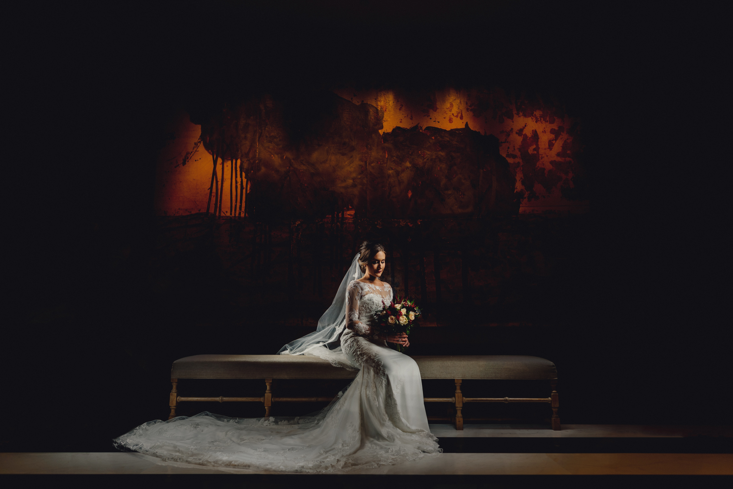 Seated bride portrait against dark background - photo by MIKI Studios