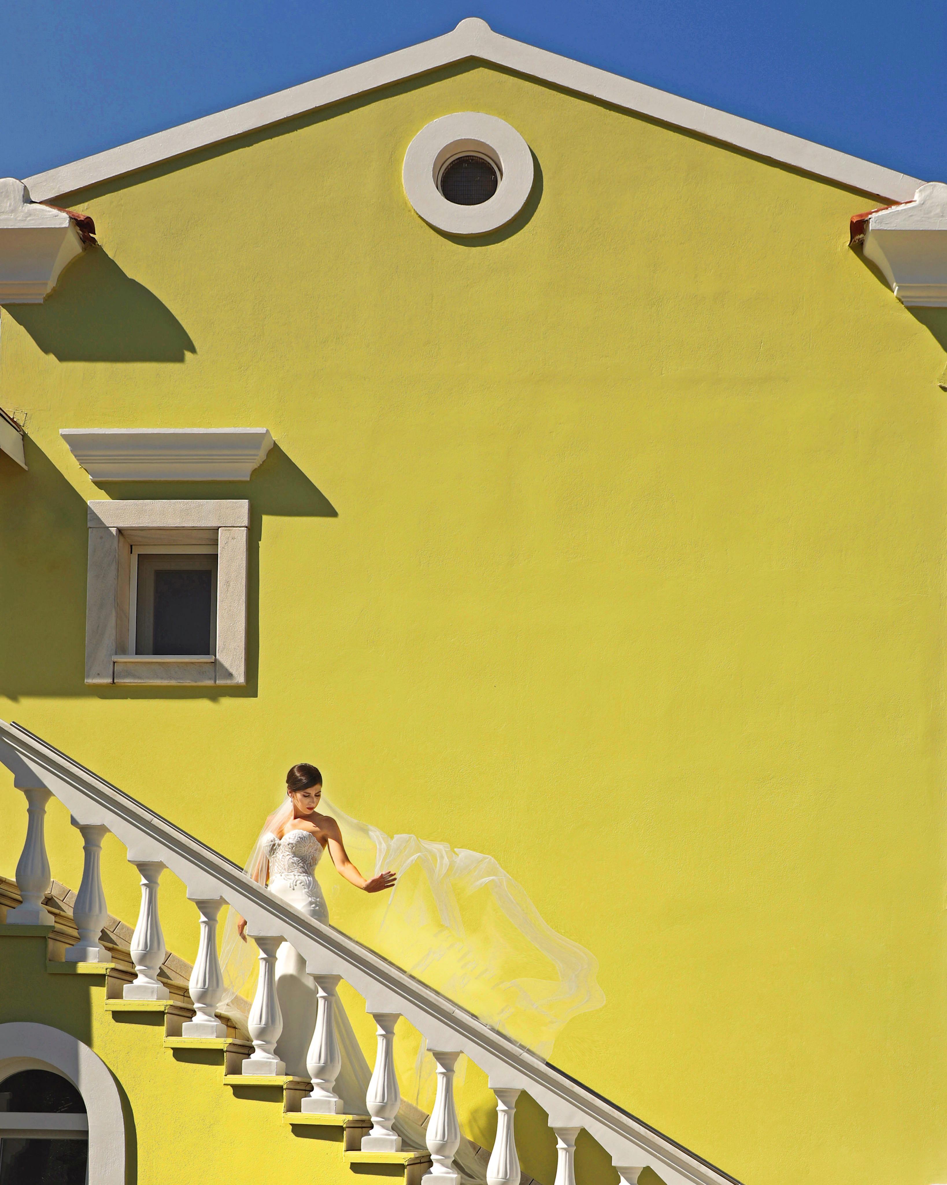 A bride on stairs against yellow colonial building - photo by Kenny Kim Photography