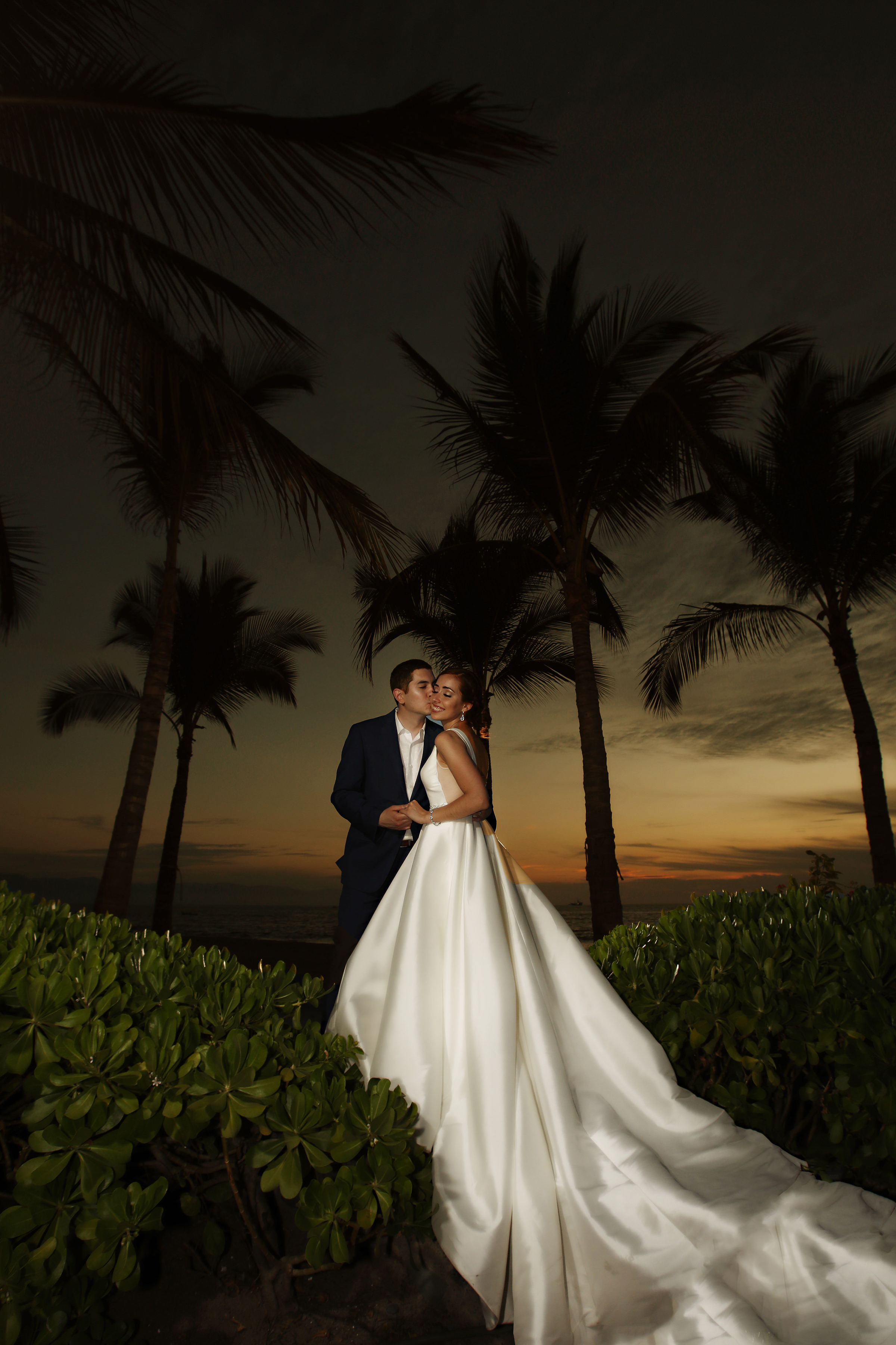 Bride and groom against tropical sunset - photo by Kenny Kim Photography