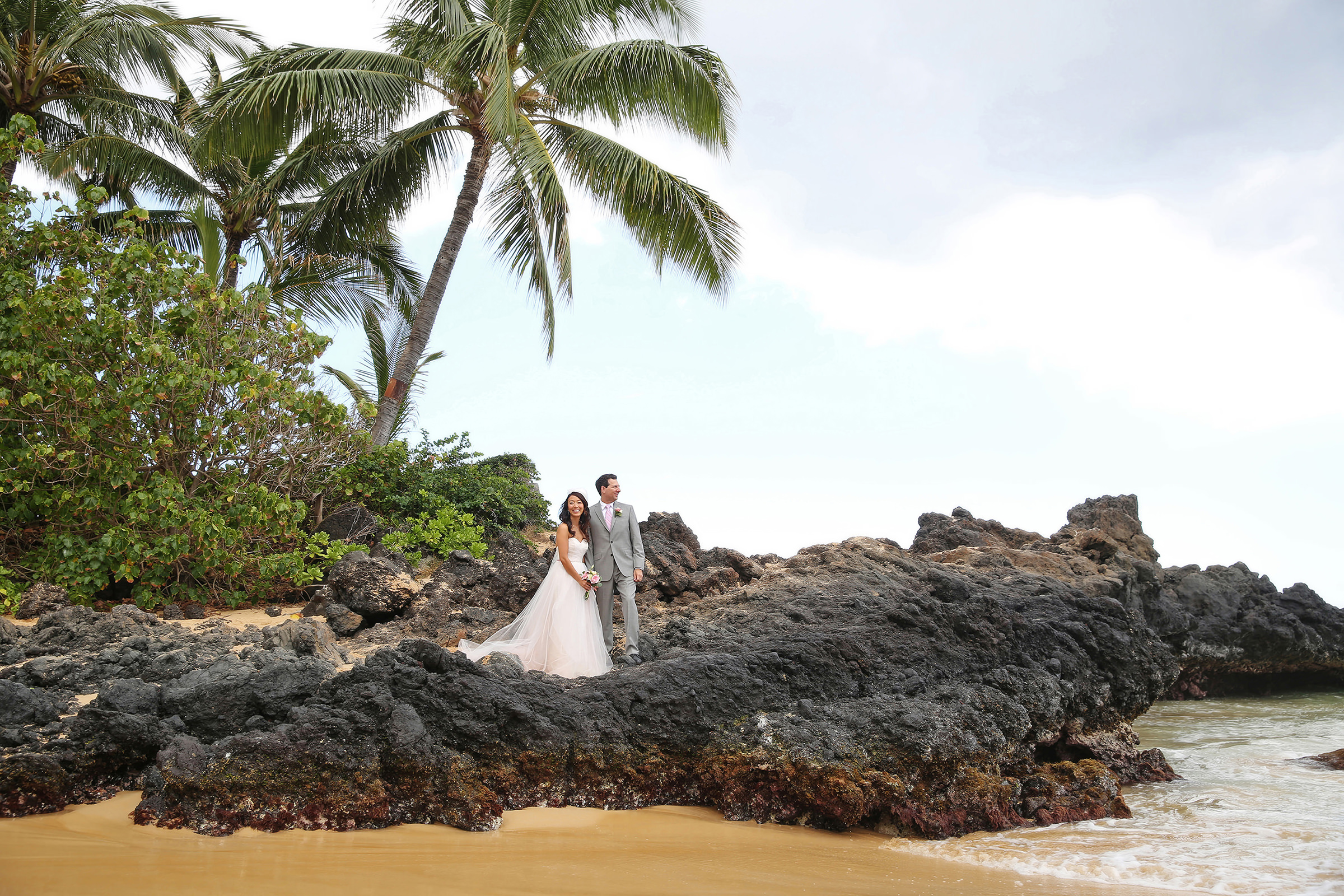 Couple on lava rock against palms and surf - photo by Kenny Kim Photography
