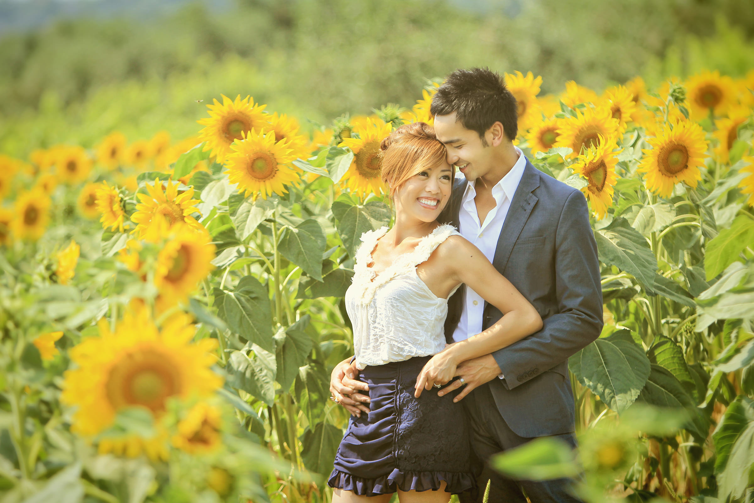 Engagement couple portrait in field of sunflowers - photo by Kenny Kim Photography