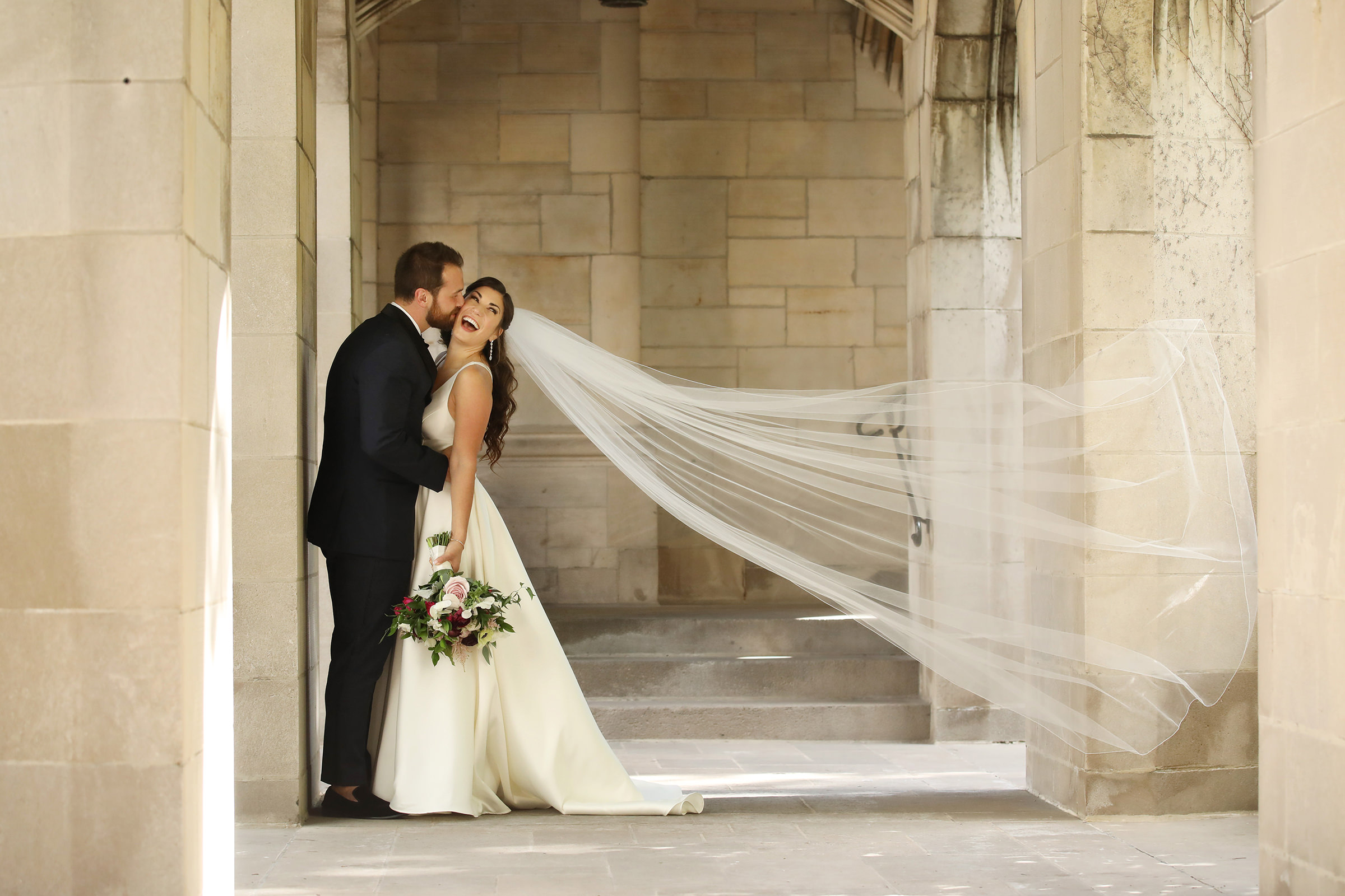 Groom kisses bride with flowing veil - photo by Kenny Kim Photography