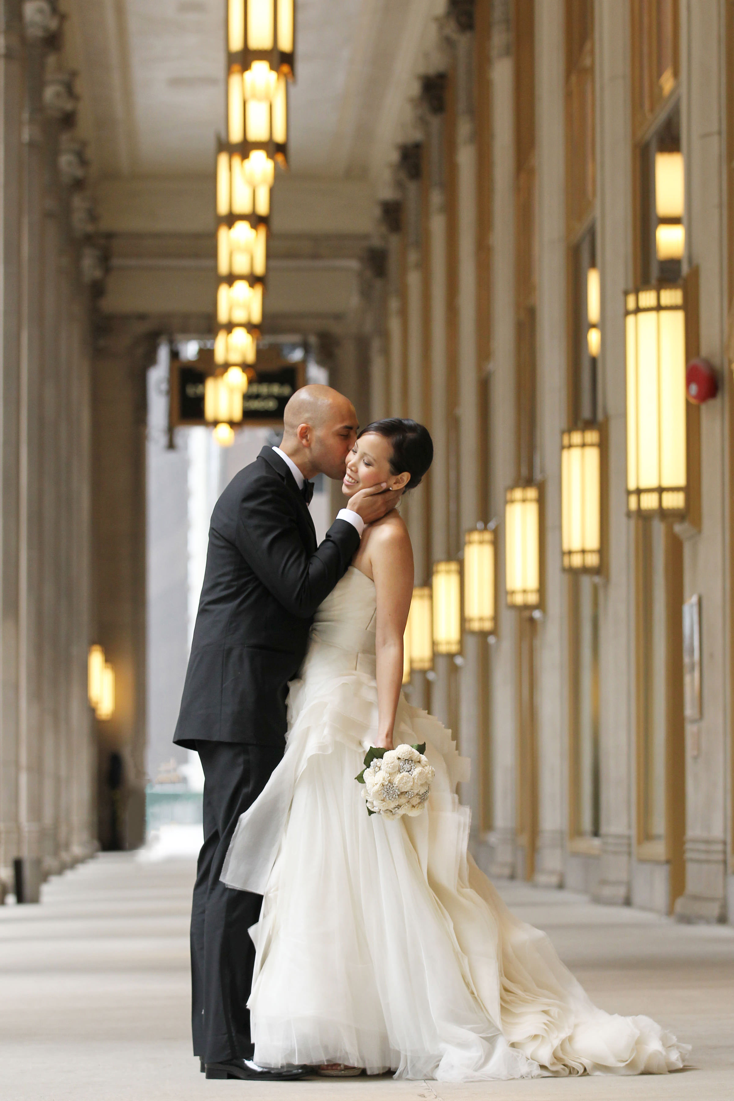 Kissing the bride against historic architecture - photo by Kenny Kim Photography