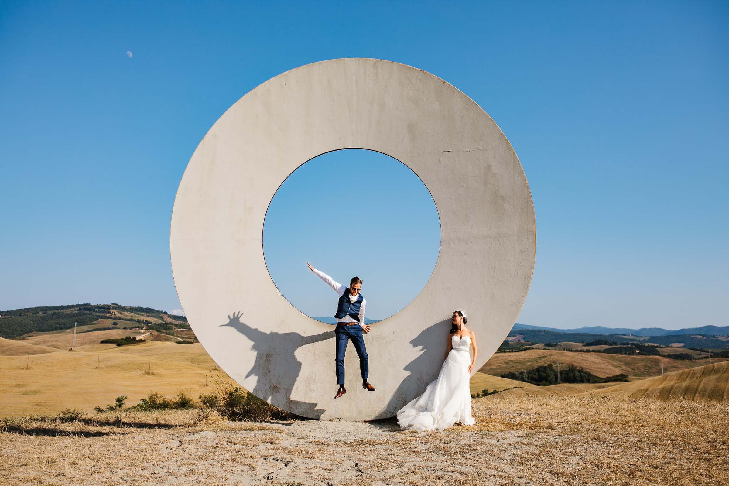 Bride and groom play on outdoor sculpture - photo by Julian Kanz Photography