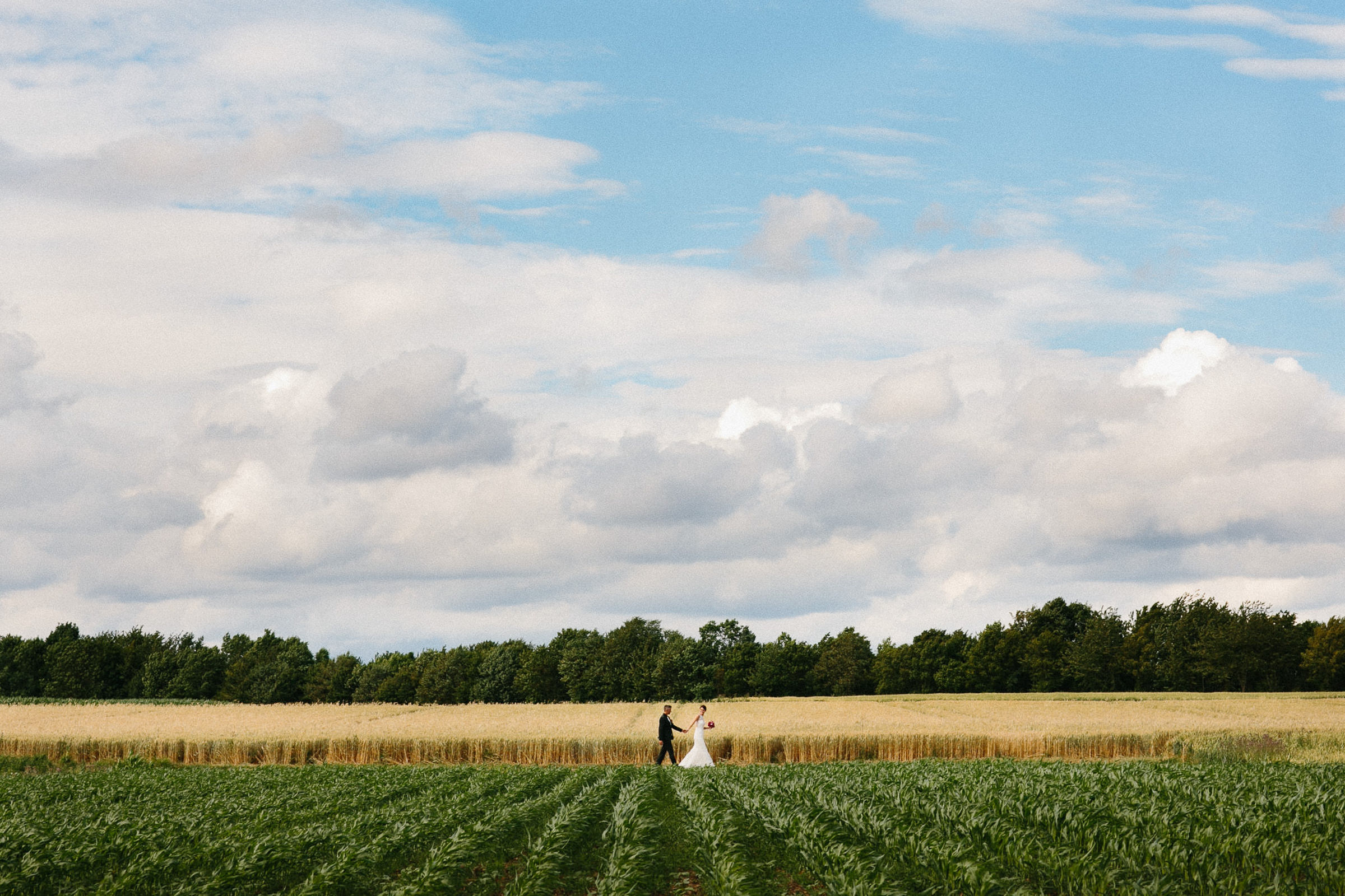Couple walks in the fields - photo by Julian Kanz Photography