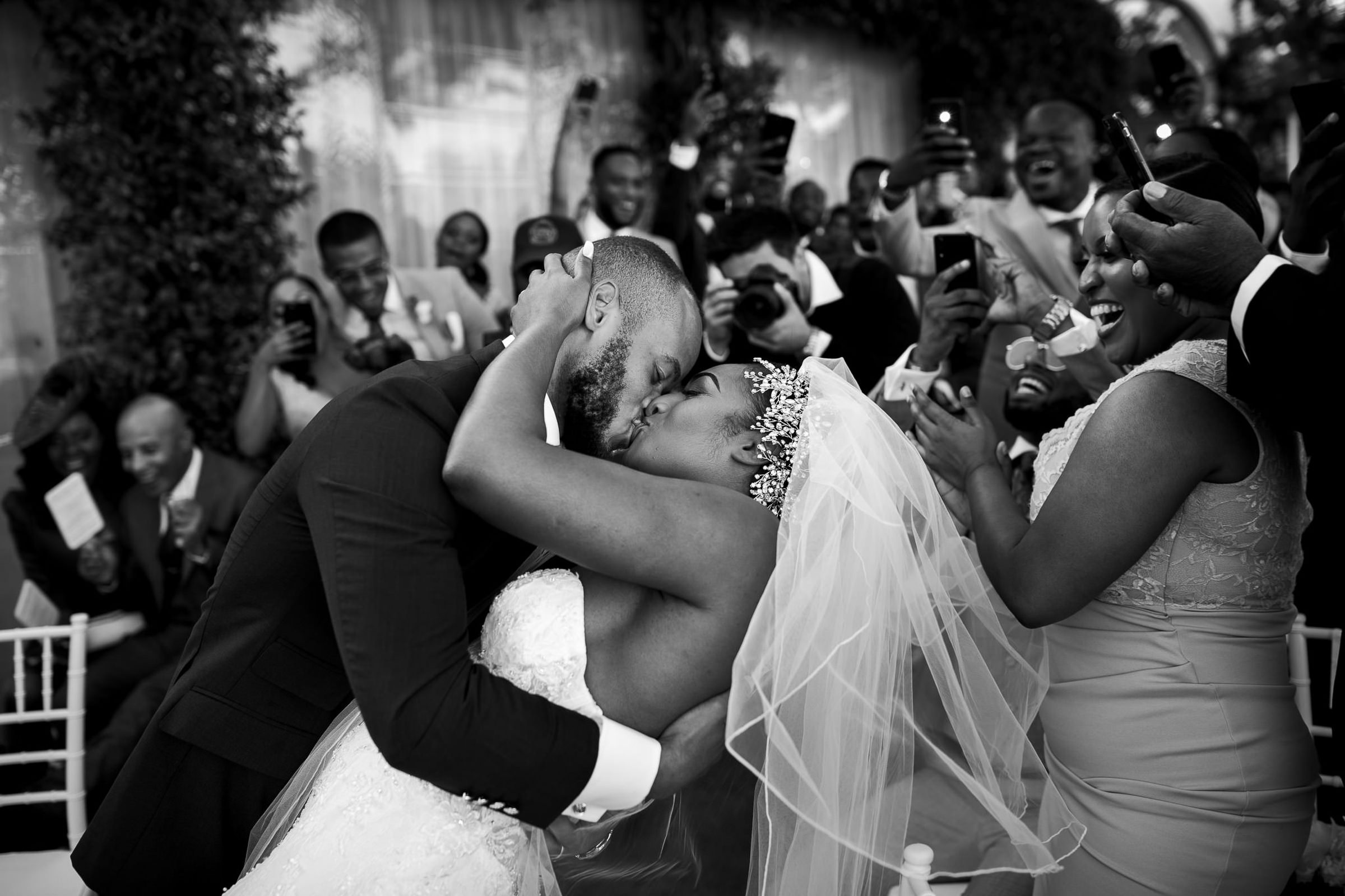 Groom dipping and kissing bride among cheers - photo by Julian Kanz Photography