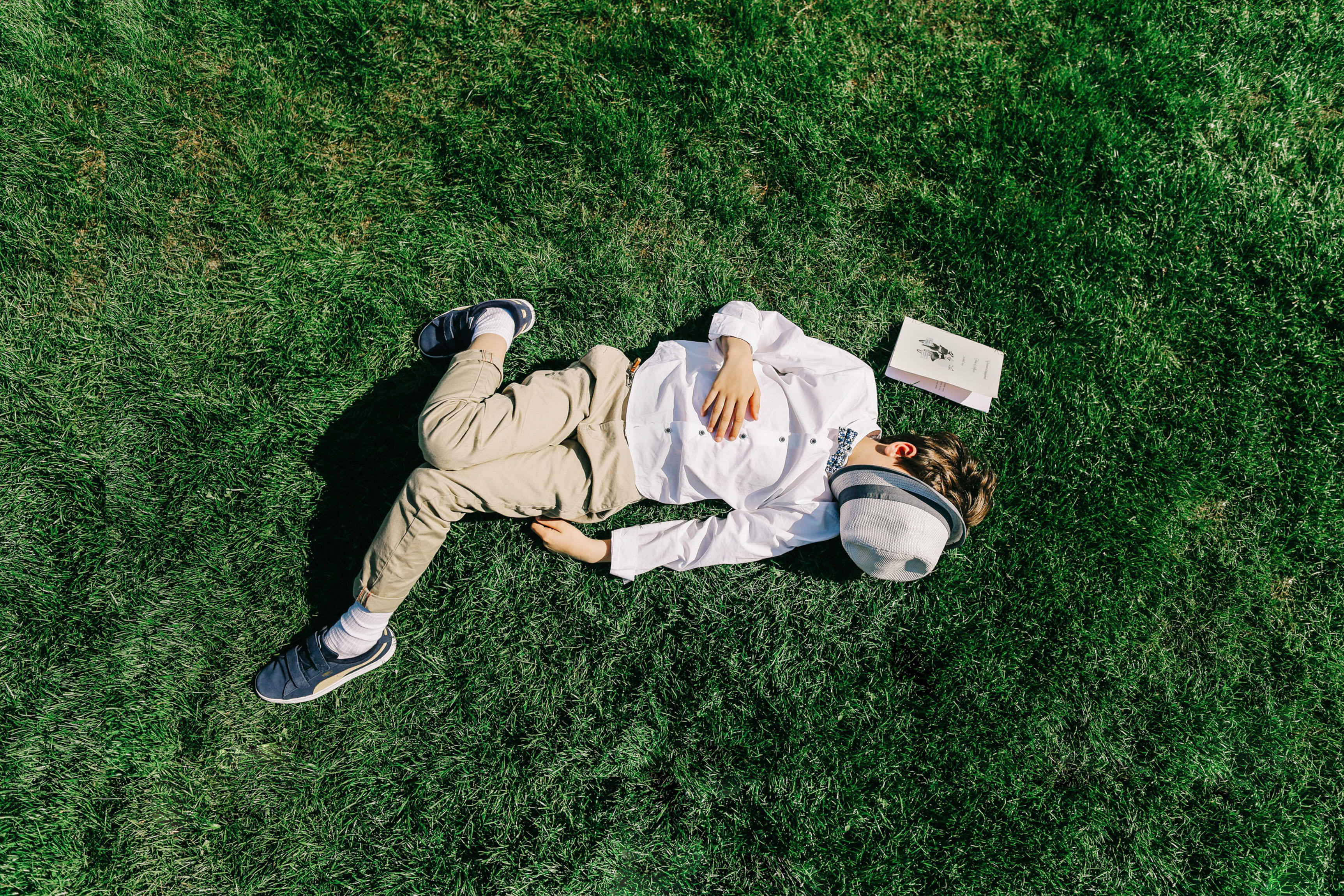 Boy resting on grass - photo by Amandine Ropars