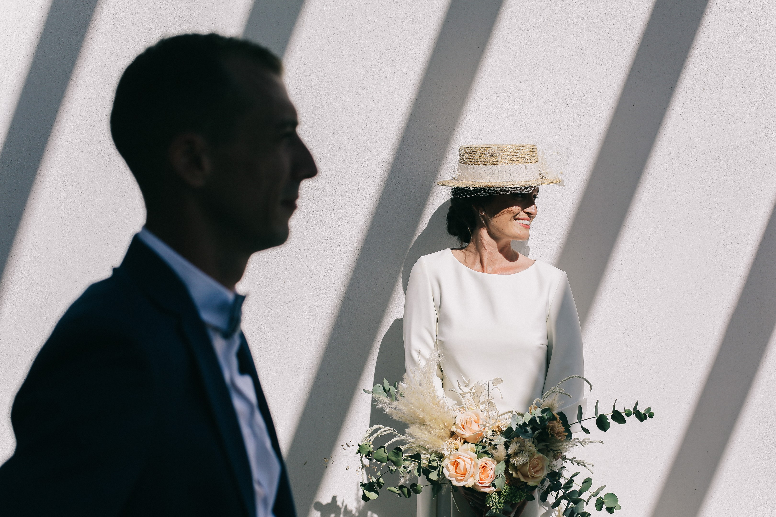 Bride in straw hat against shadowed ball - photo by Amandine Ropars