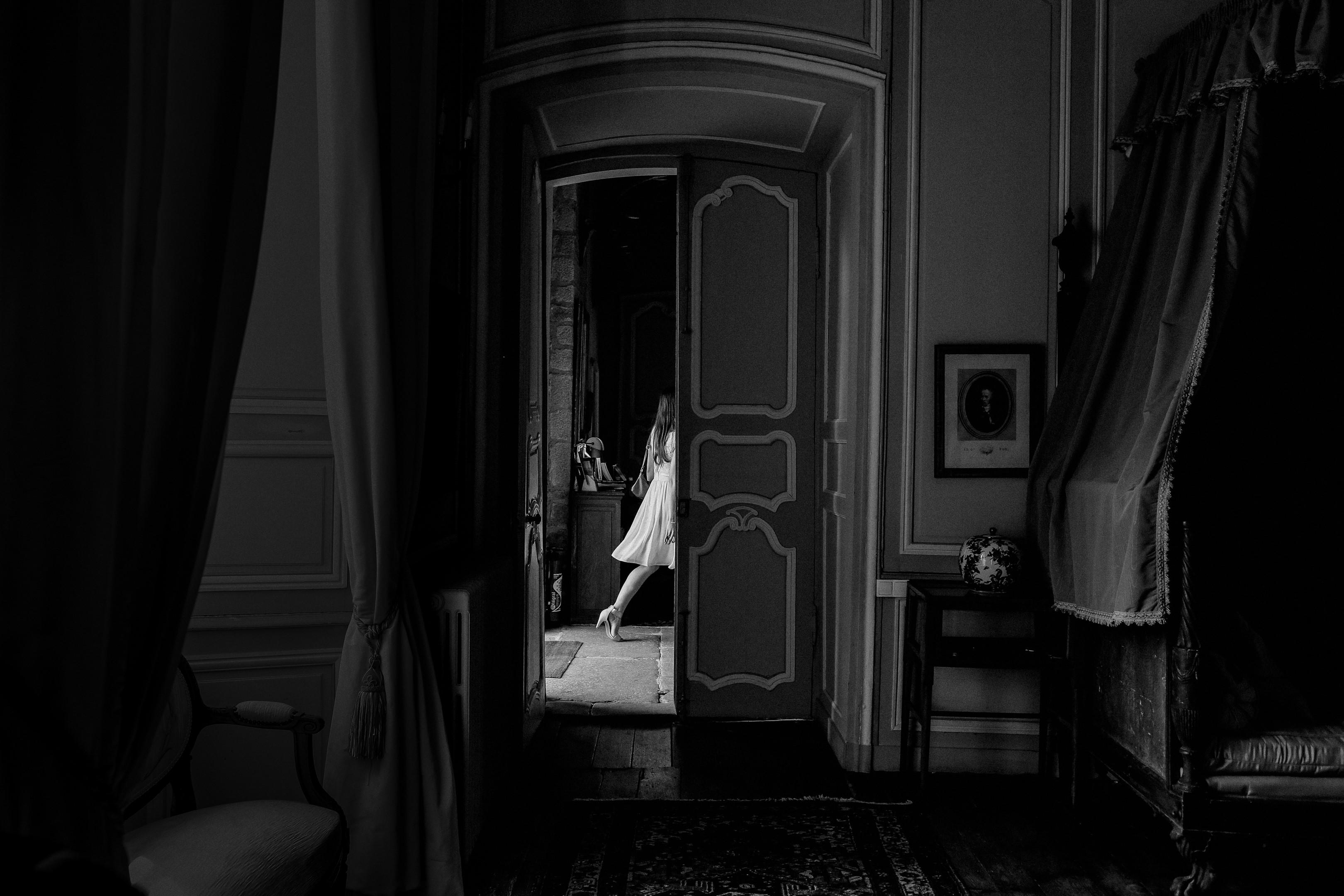 walking bride seen through interior doorway - photo by Amandine Ropars