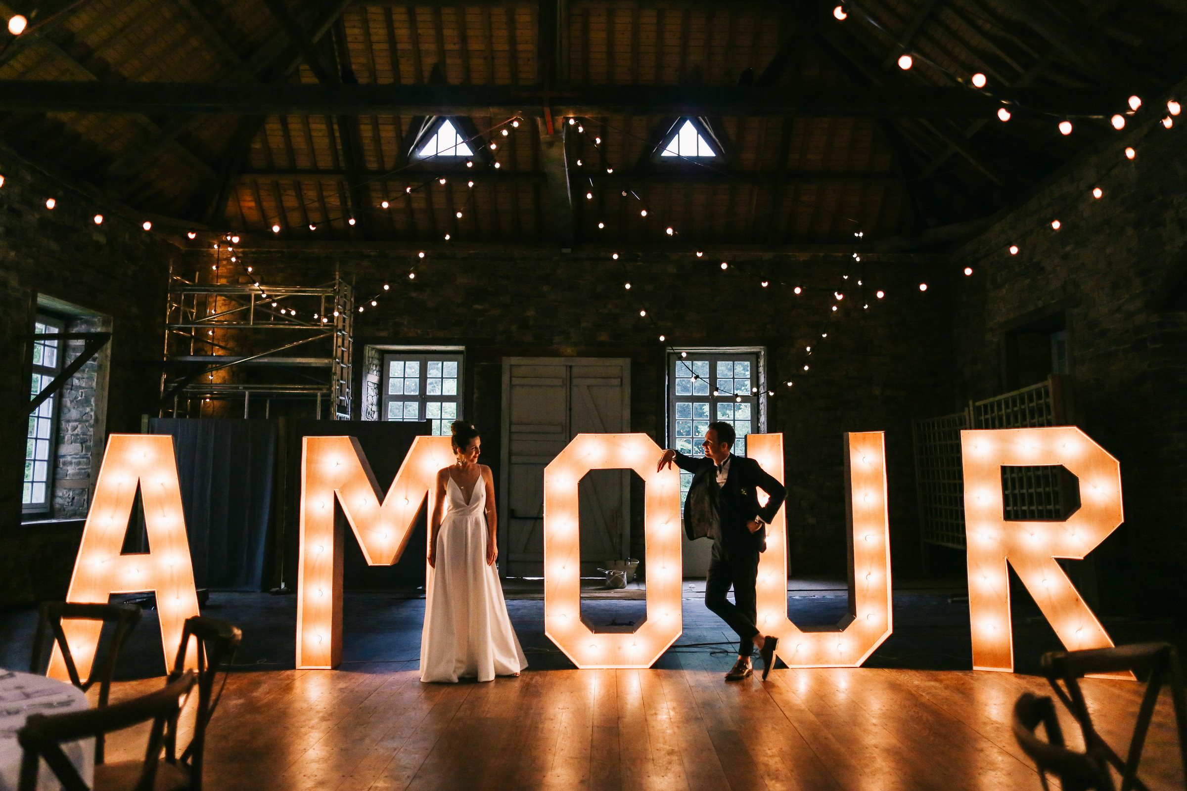 bride and groom portrait in front of light letters- photo by Amandine Ropars, france