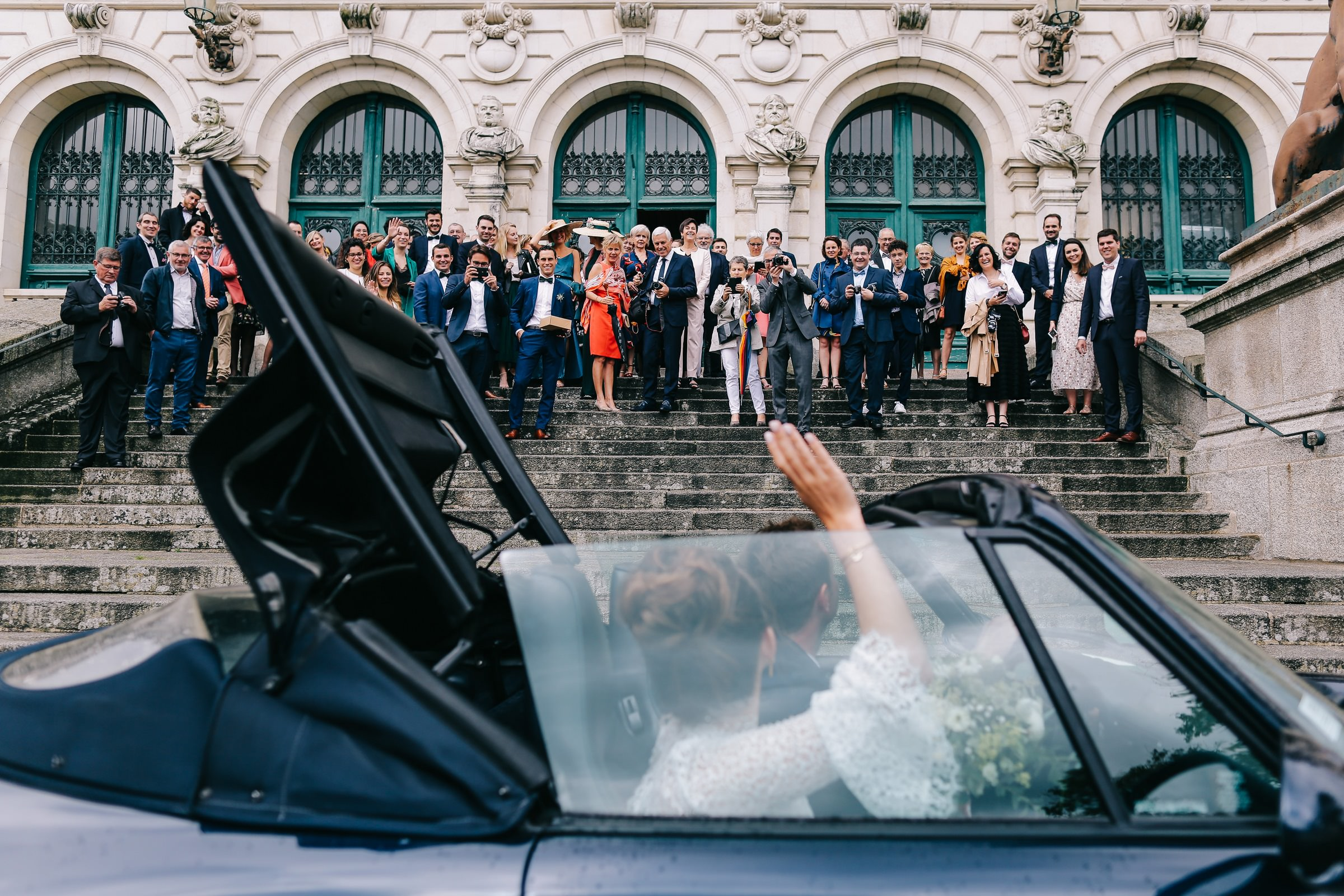 bride and groom waving to guests while driving away- photo by Amandine Ropars, france