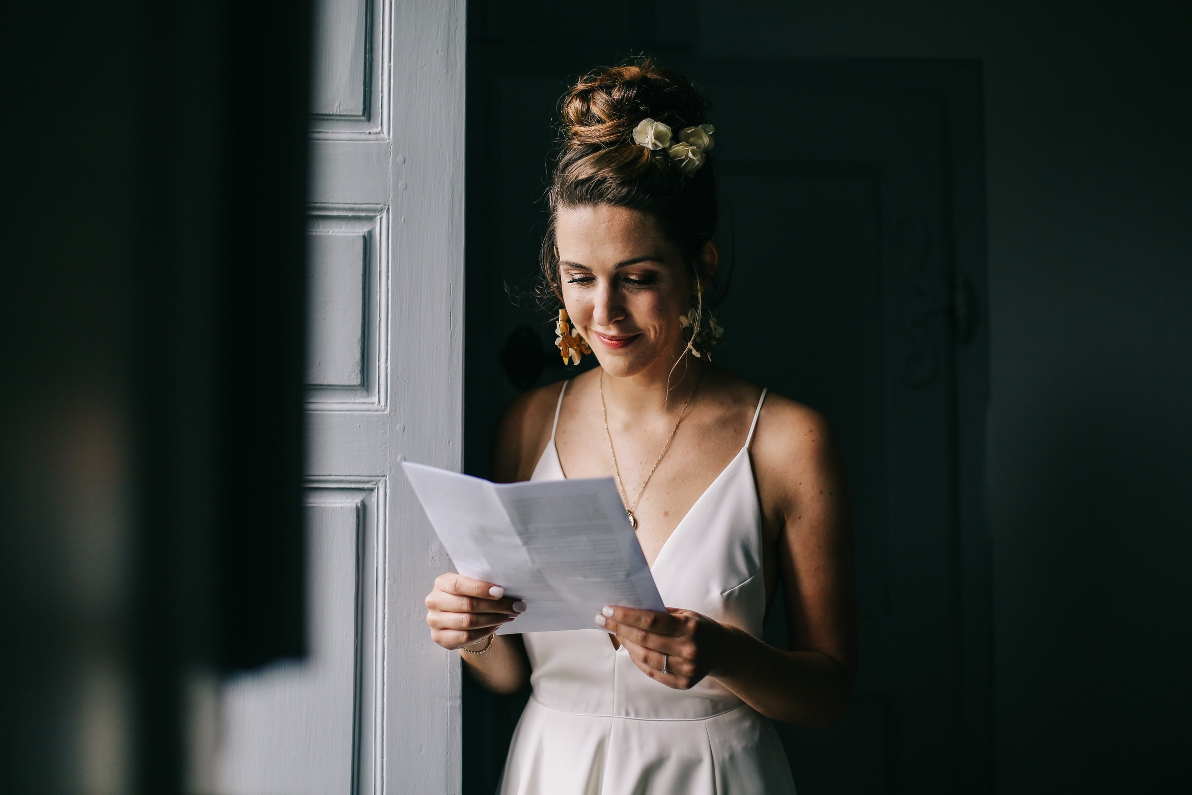 bride reading letter in window light - photo by Amandine Ropars
