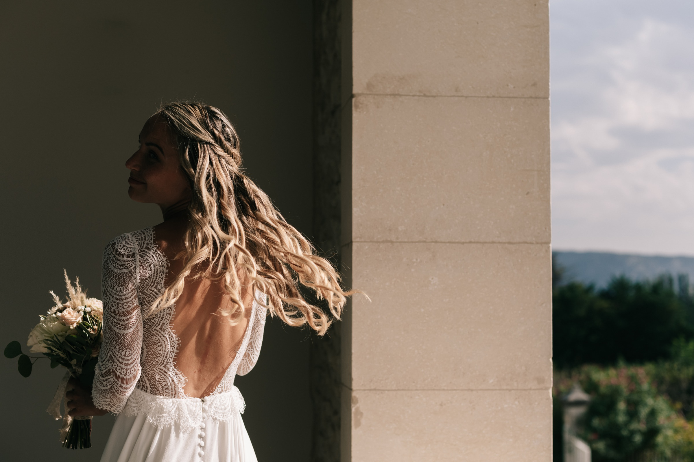 bride whipping her hair with backless dress- photo by Amandine Ropars, france