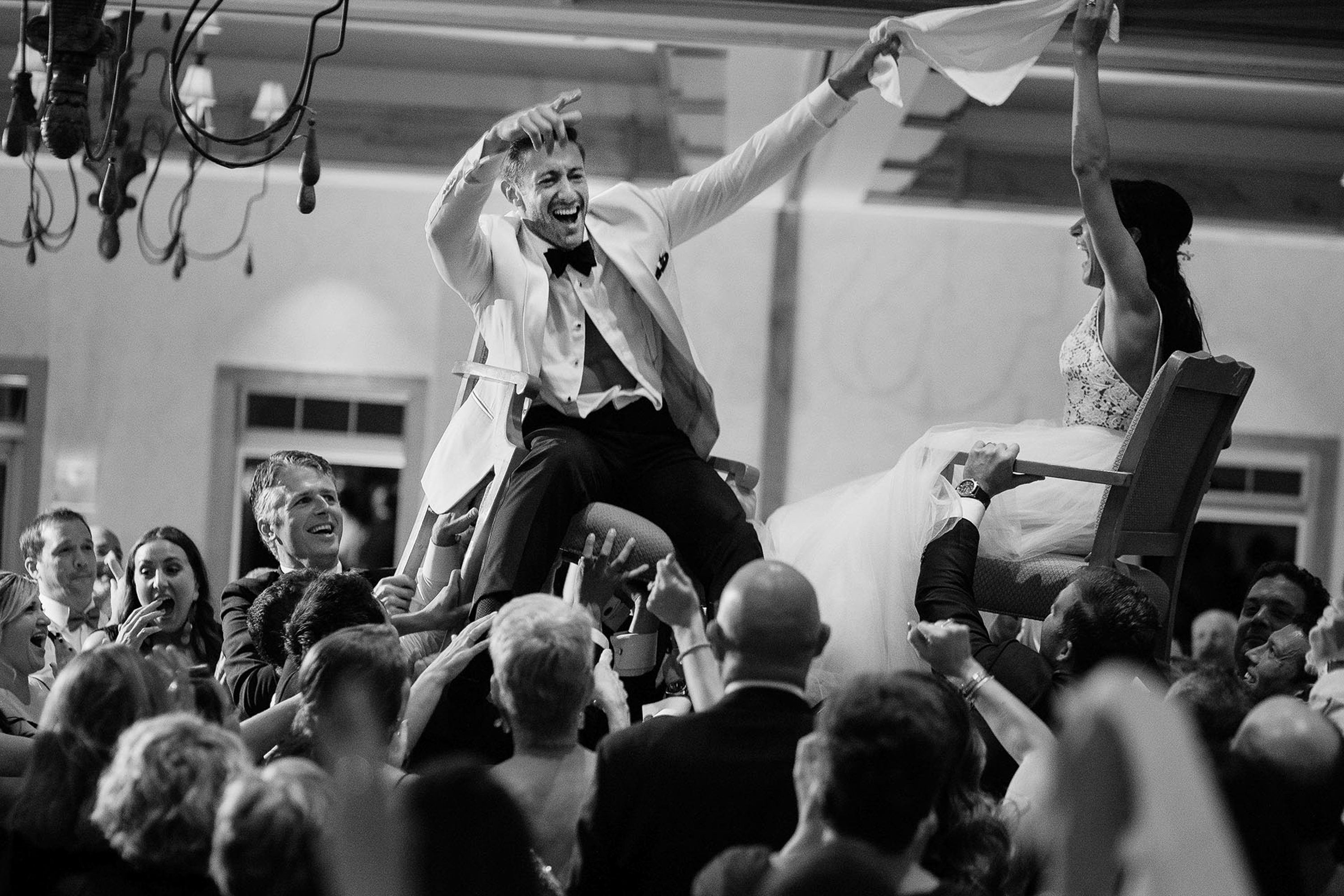 Action shot of bride and groom dancing on lifted chairs - photo by Alex Paul Photography