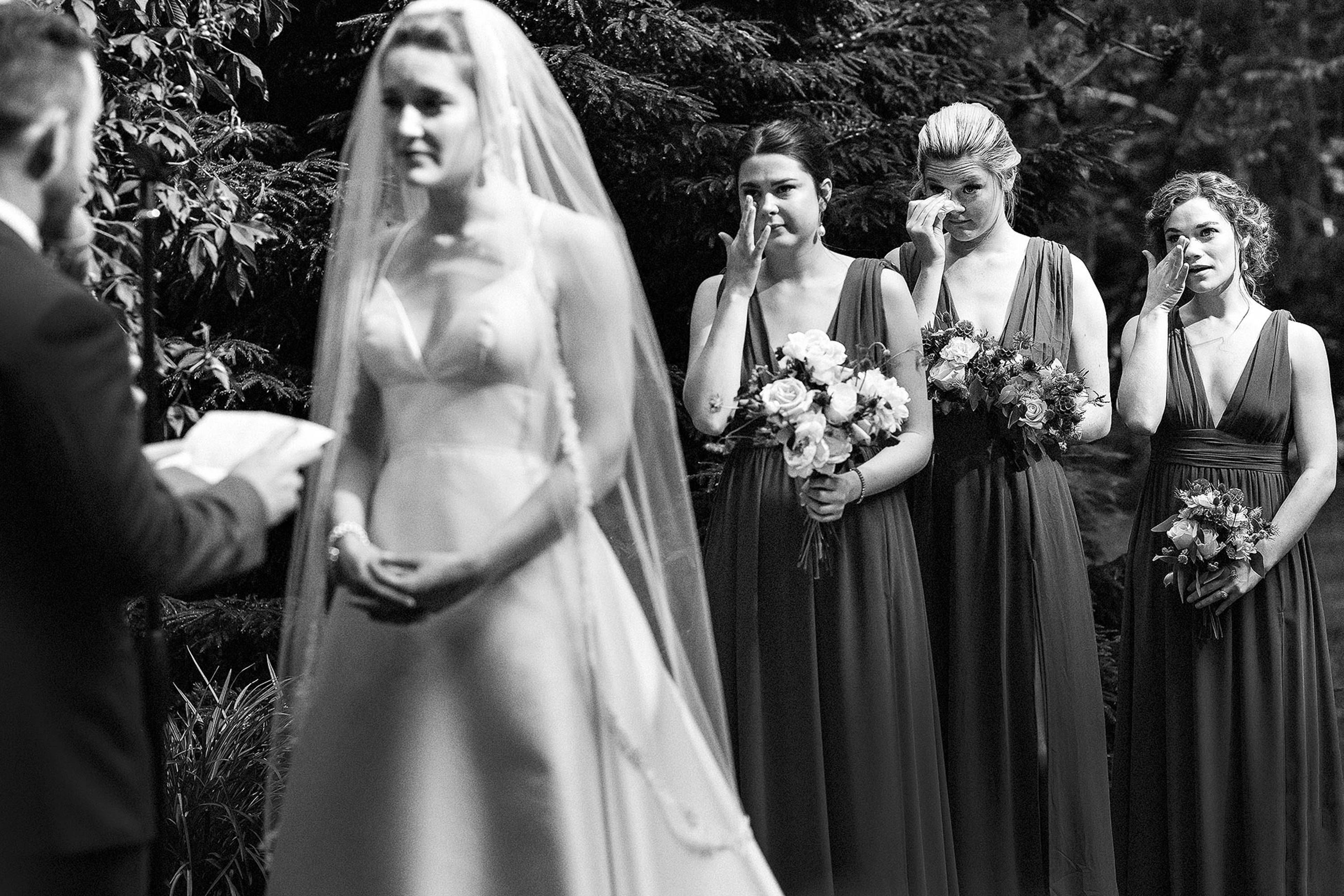 Bridesmaids wipe tears during ceremony - photo by Alex Paul Photography