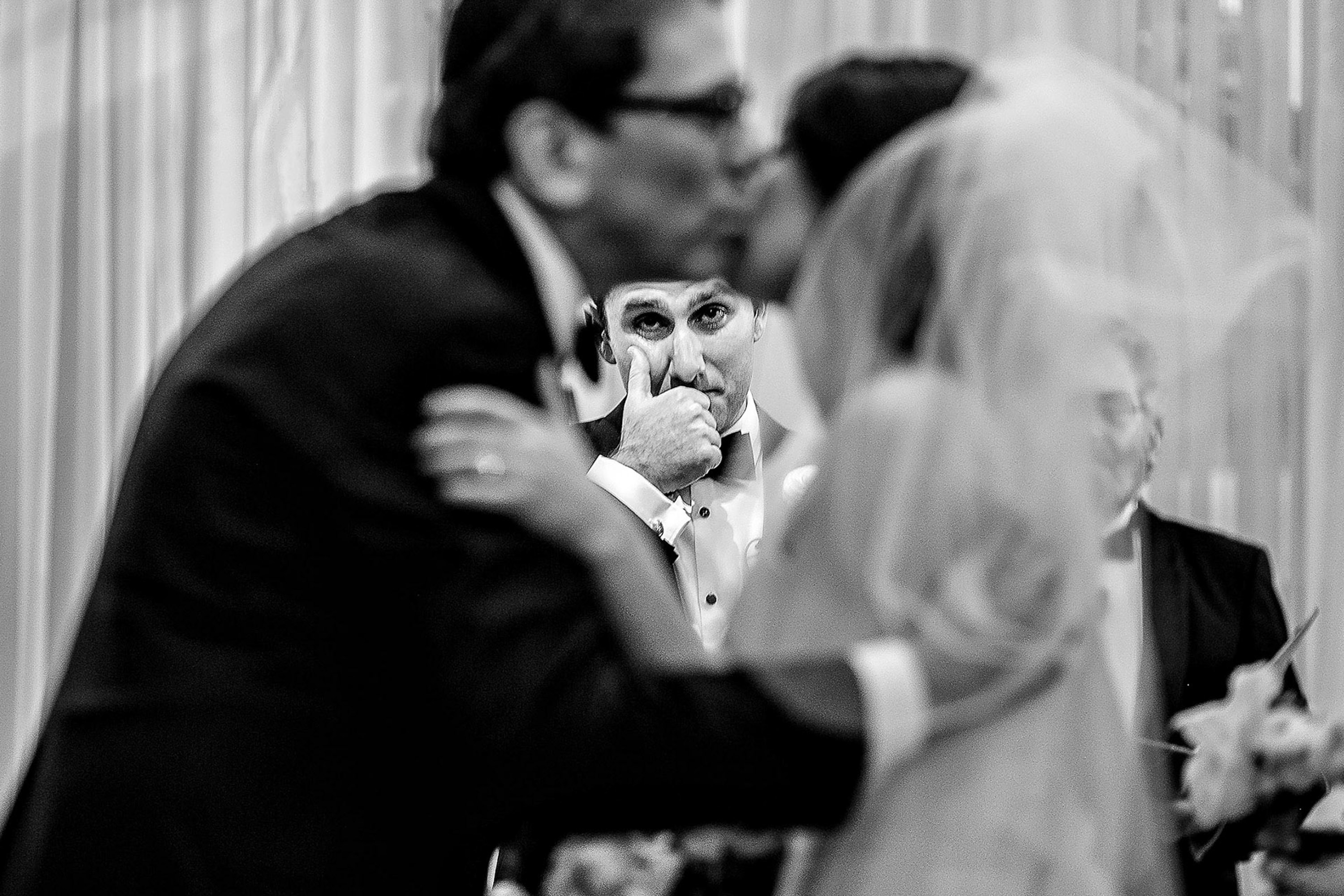 Ceremonial couple kiss with onlooker - photo by Alex Paul Photography