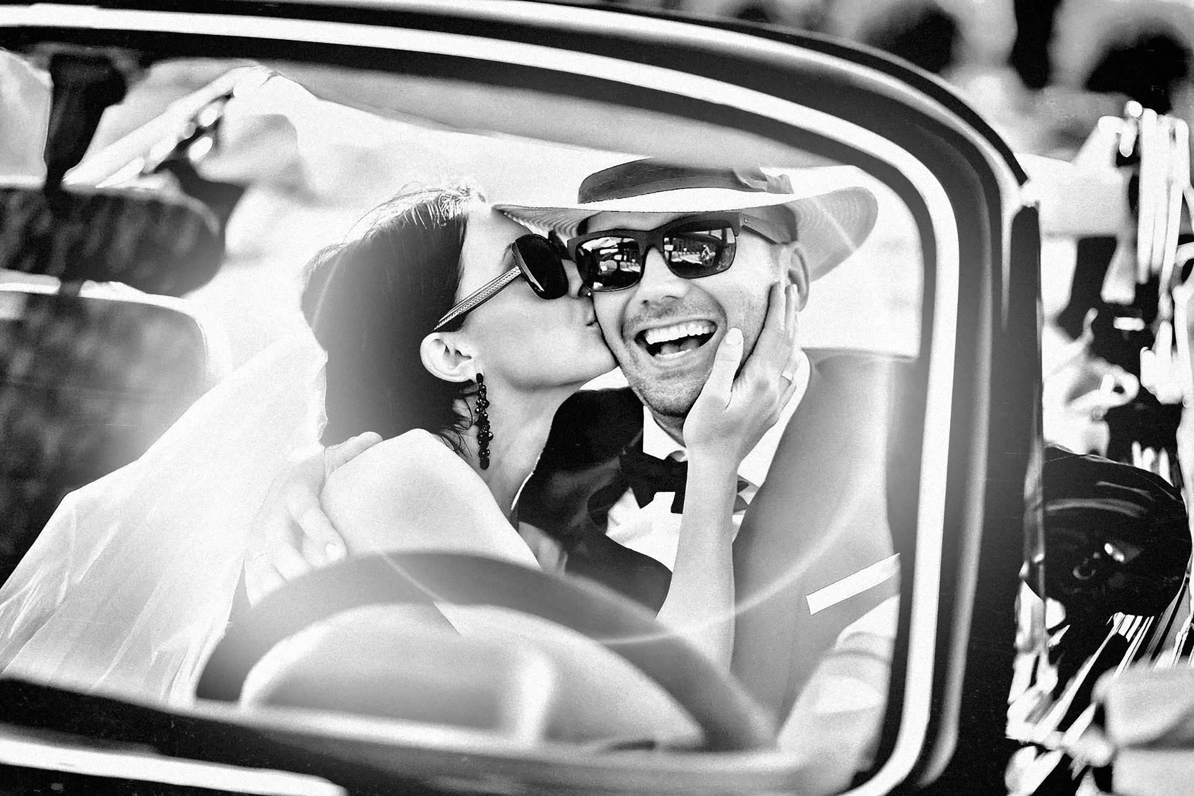 Happy sunglasses kiss seen through windshield - photo by Alex Paul Photography