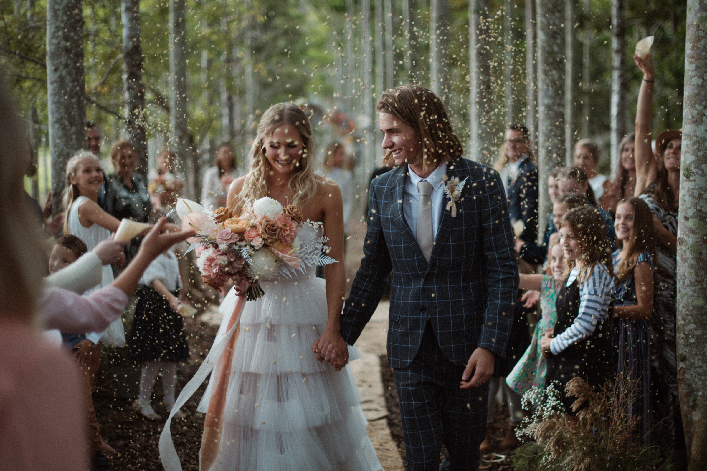 Couple exits  ceremony amid rice and trees - photo by Ben Sowry Photo