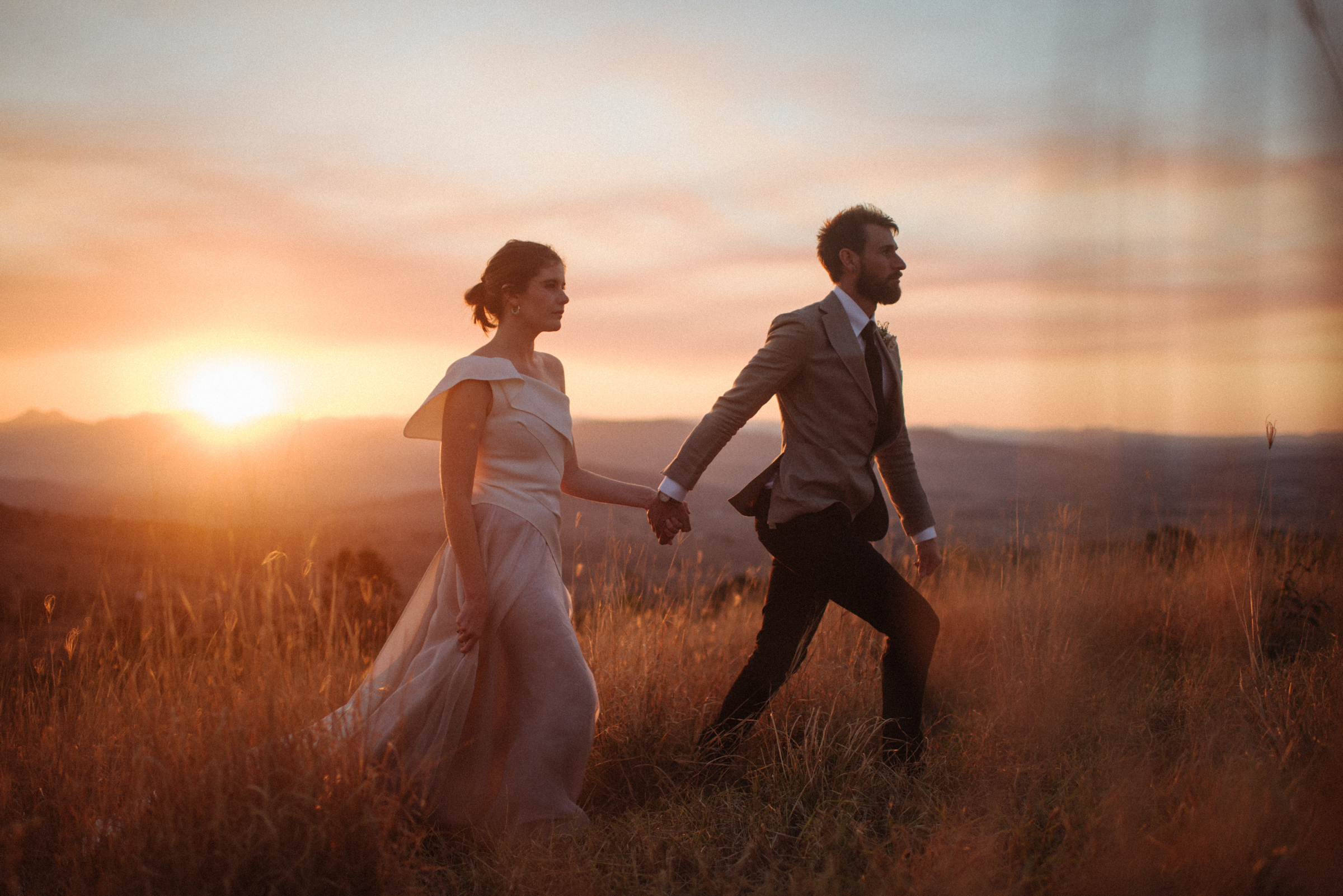 Couple walking in field at sunset - photo by Ben Sowry Photo