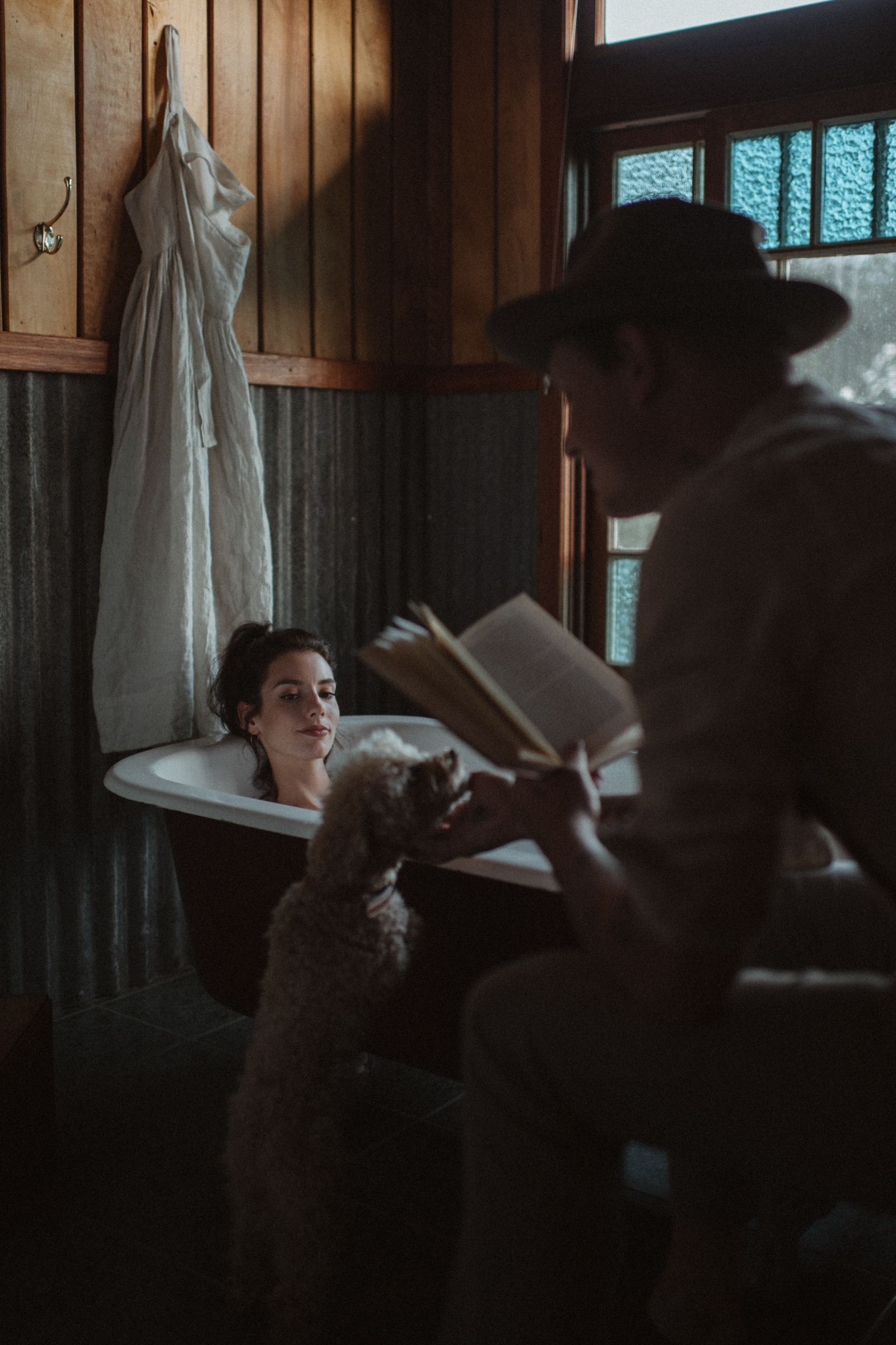 Groom reads to bride in bath - photo by Ben Sowry Photo