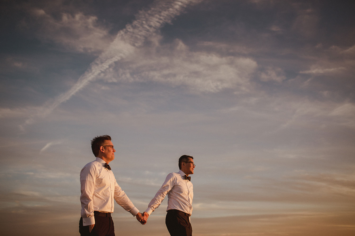 2 grooms holding hands against blue sky - photo by Motiejus