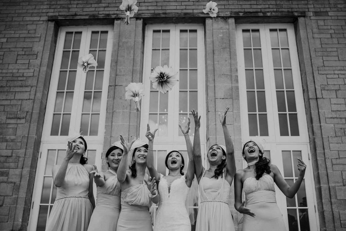 Bridal party throwing bouquets in the air - photo by Motiejus