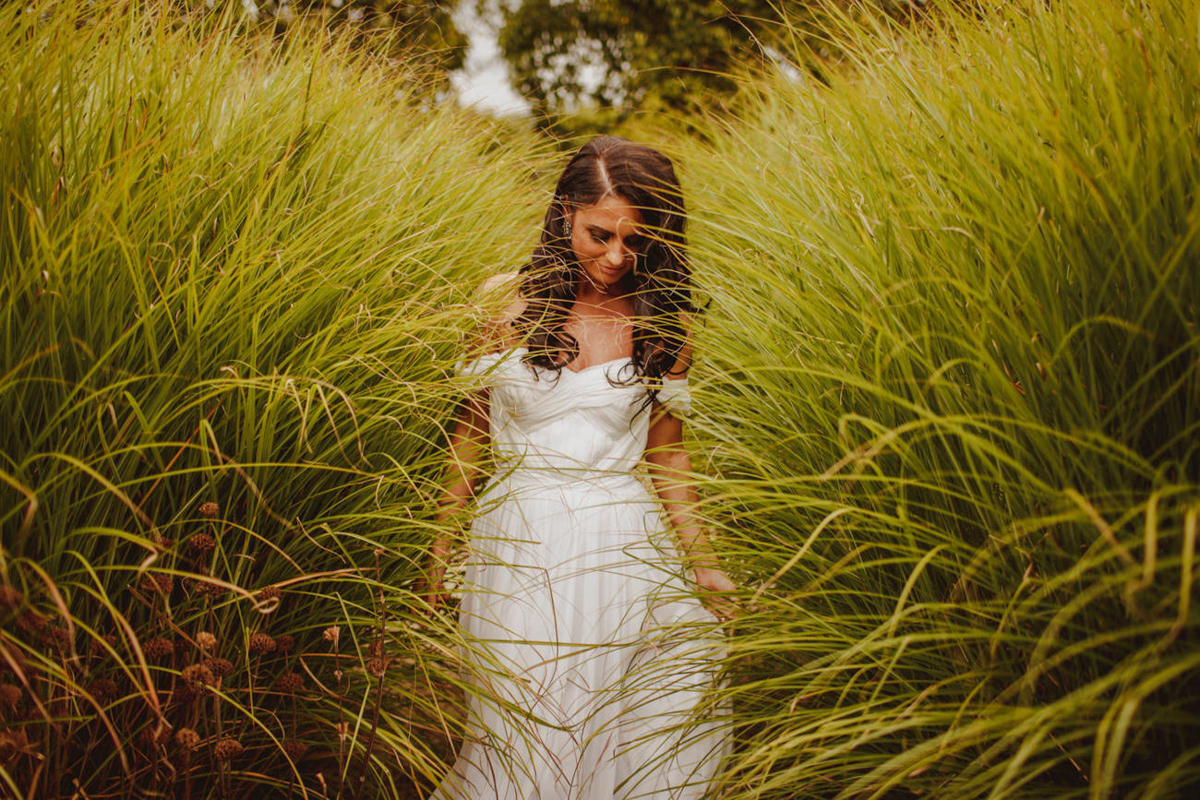 Bride portrait in tall grasses - photo by Motiejus