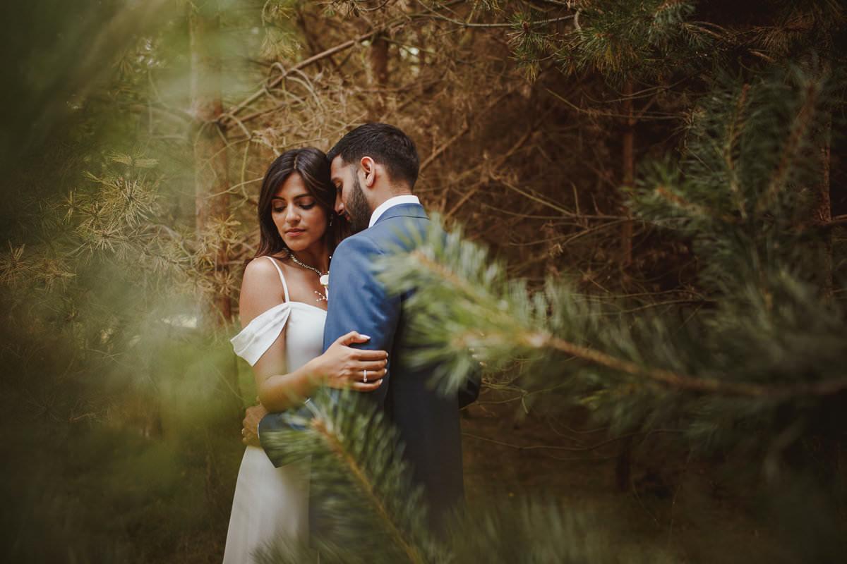 Couple portrait through evergreen trees -- photo by Motiejus