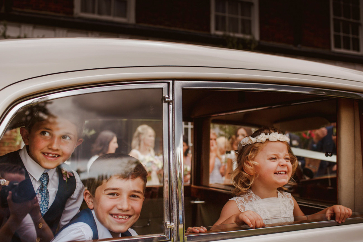 Kids in car press their faces against window - photo by Motiejus - UK wedding photographer