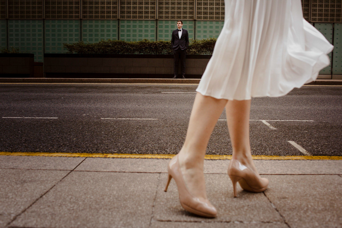 Legs of the bride with groom in background - photo by Motiejus