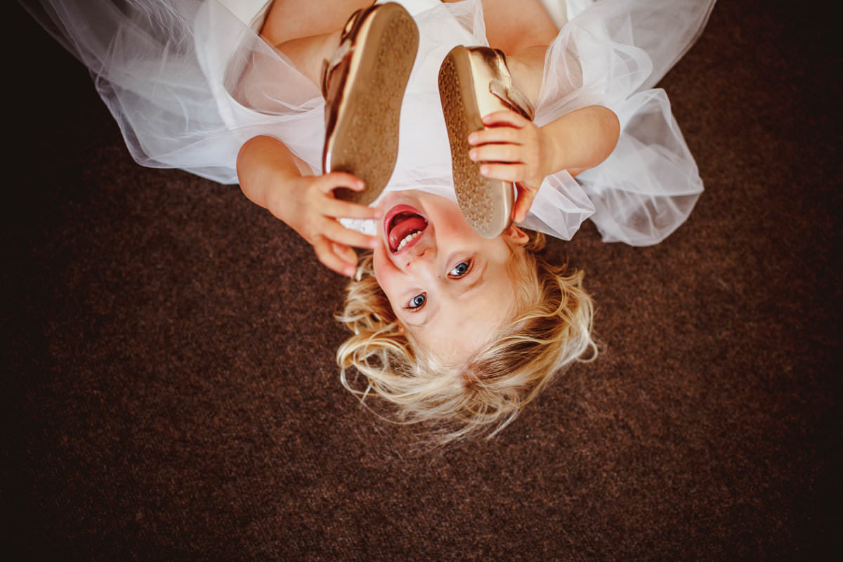 Little flower girl grabbing her feet - photo by Motiejus - London weding photographer
