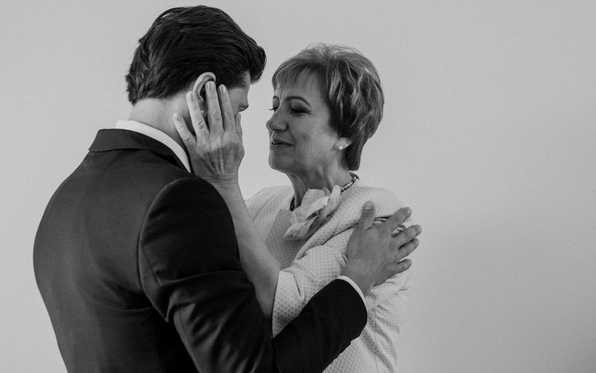 Mom holds her son's face in her hands - photo by Motiejus - UK wedding photographer