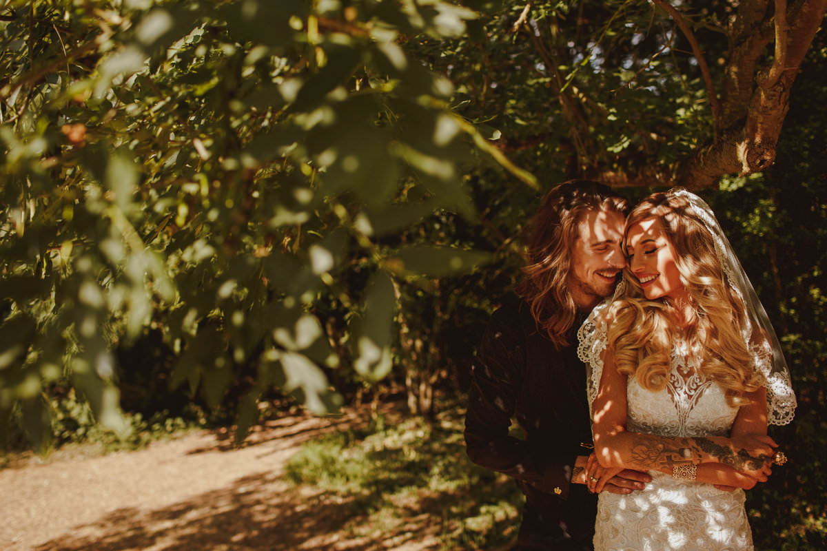 Couple embrace under tree in dappled sunlight - photo by Motiejus