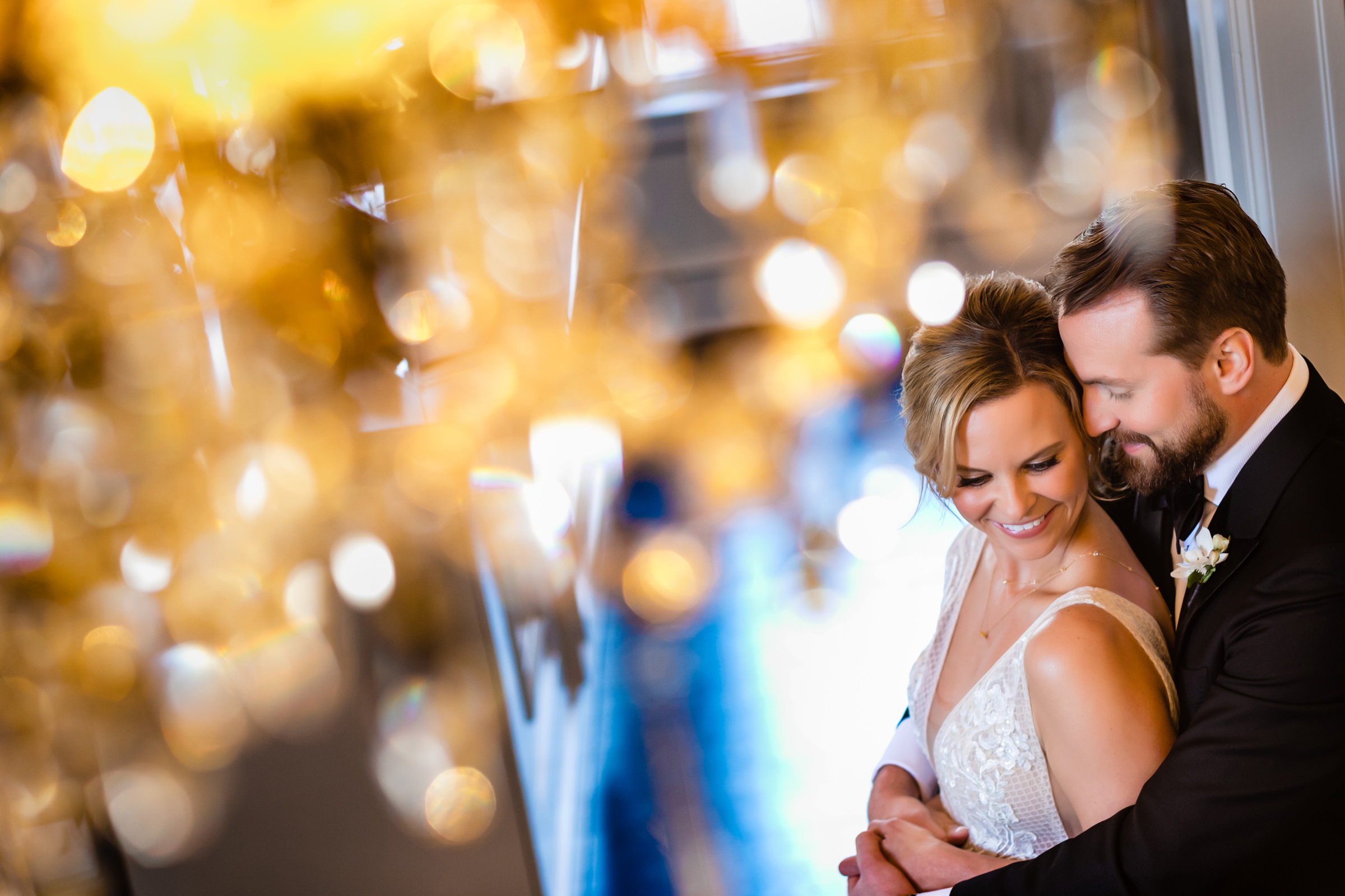 Bokeh lit couple embrace - photo by Jenny DeMarco Photography