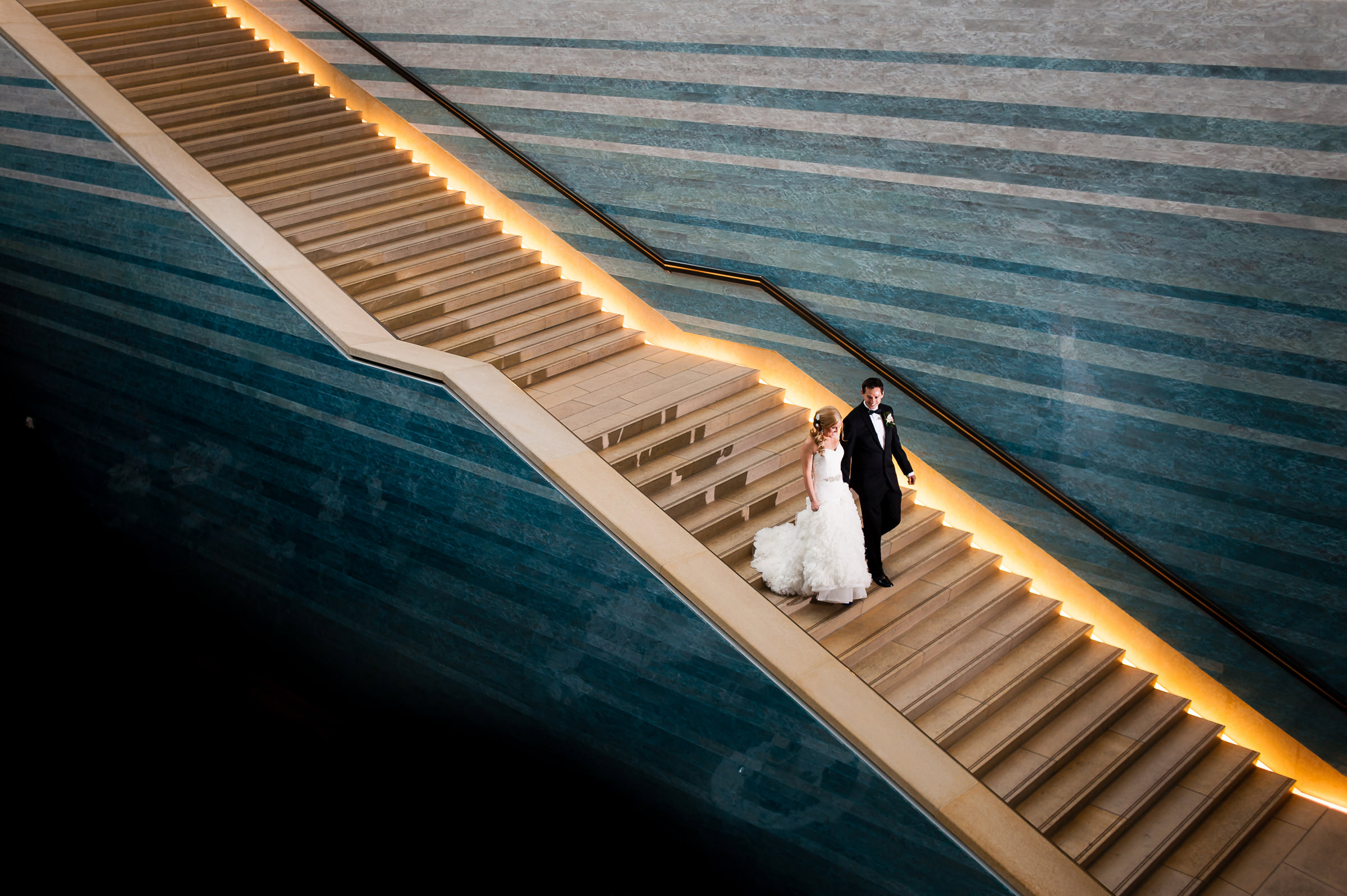 Couple descending epic staircase - photo by Jenny DeMarco Photography
