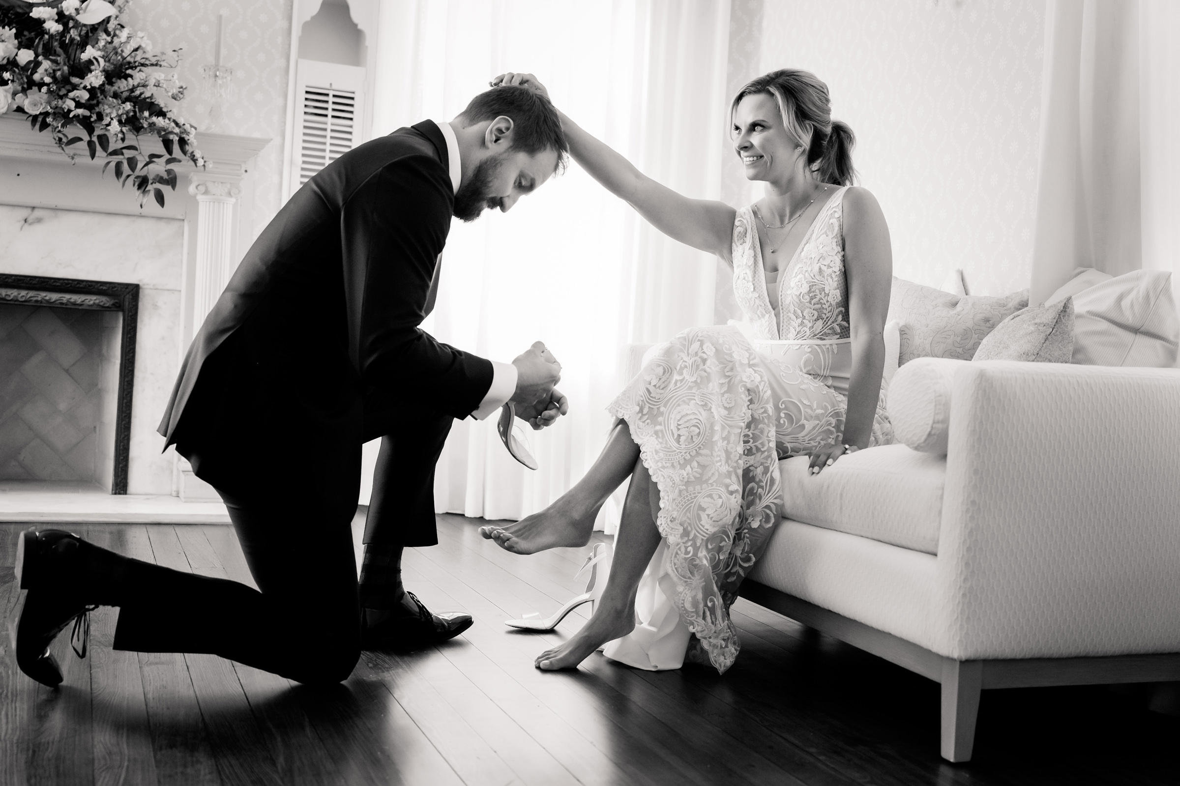 Groom kneeling with brides shoe - photo by Jenny DeMarco Photography