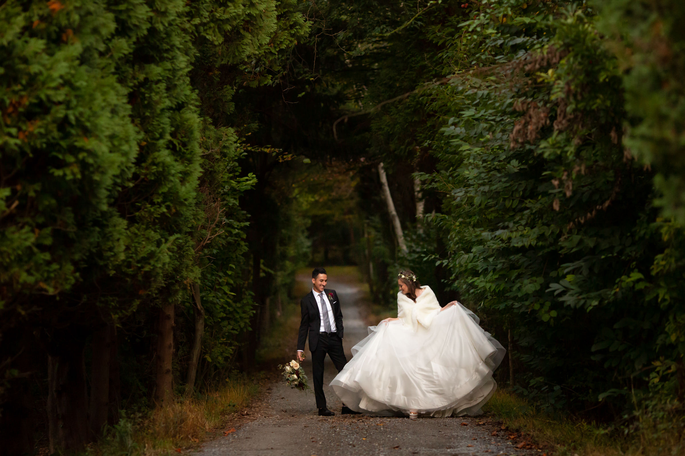 Bride in voluminous gown with groom on country road - photo by Procopio Photography