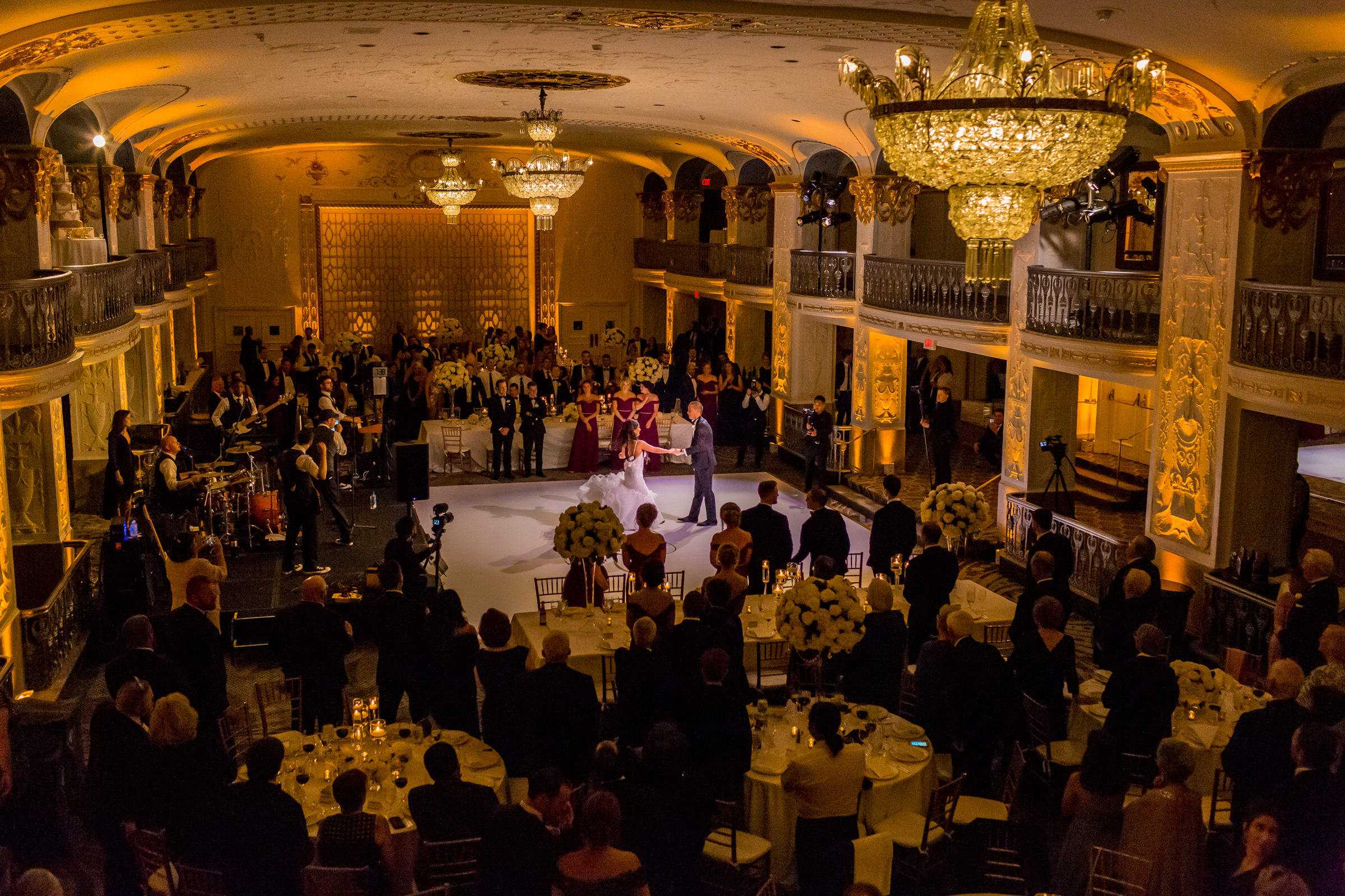 Balcony view of first dance amidst standing guests - photo by Procopio Photography