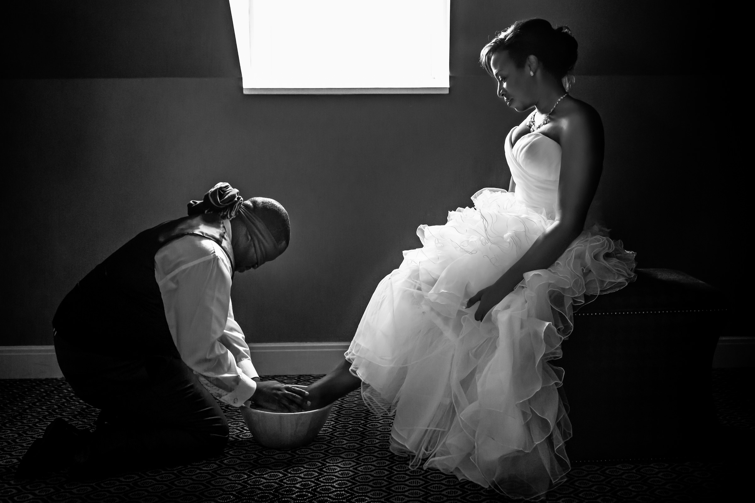 Blindfolded groom washing bride's feet - photo by Procopio Photography