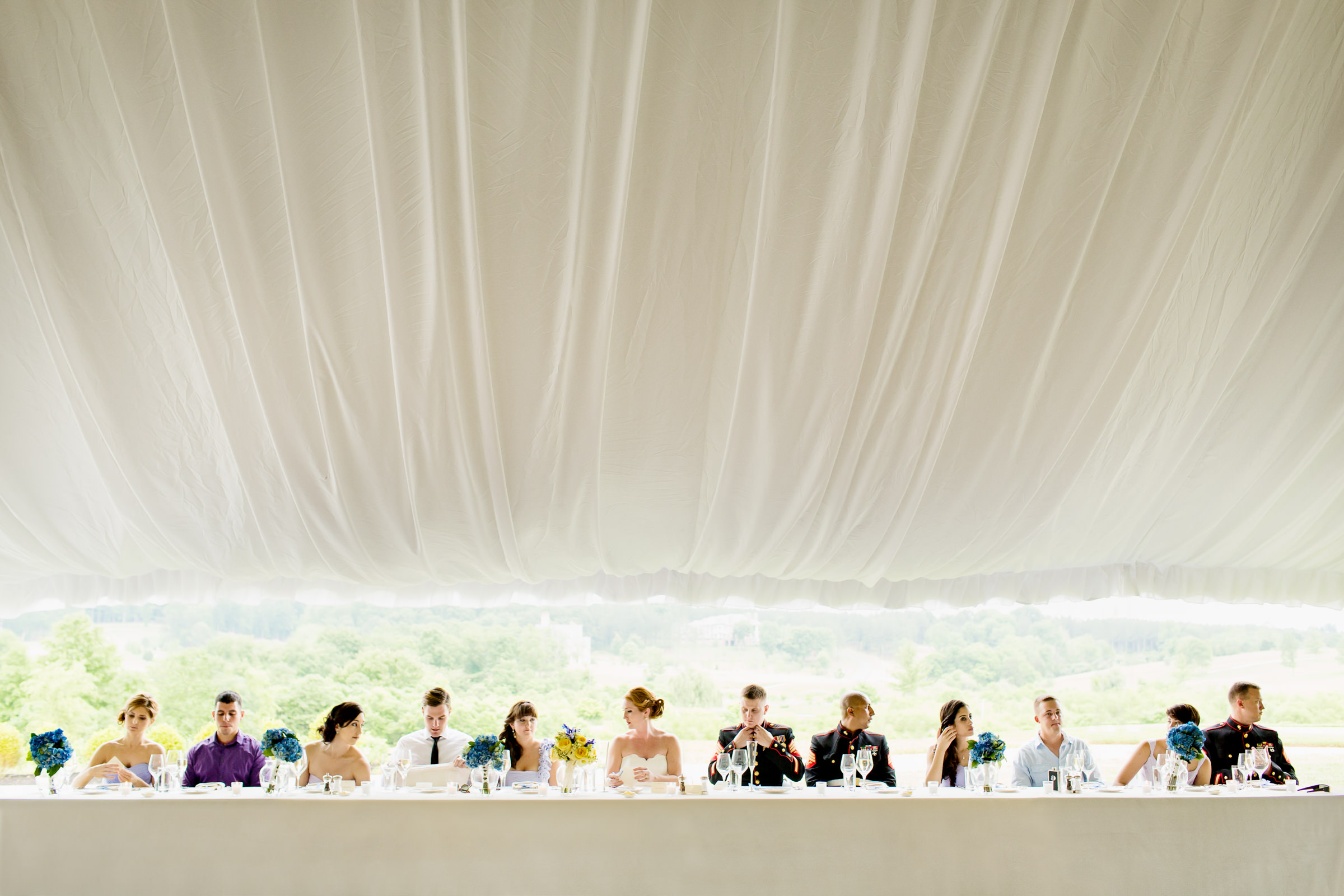 Bridal party at long table under big white tent - photo by Procopio Photography