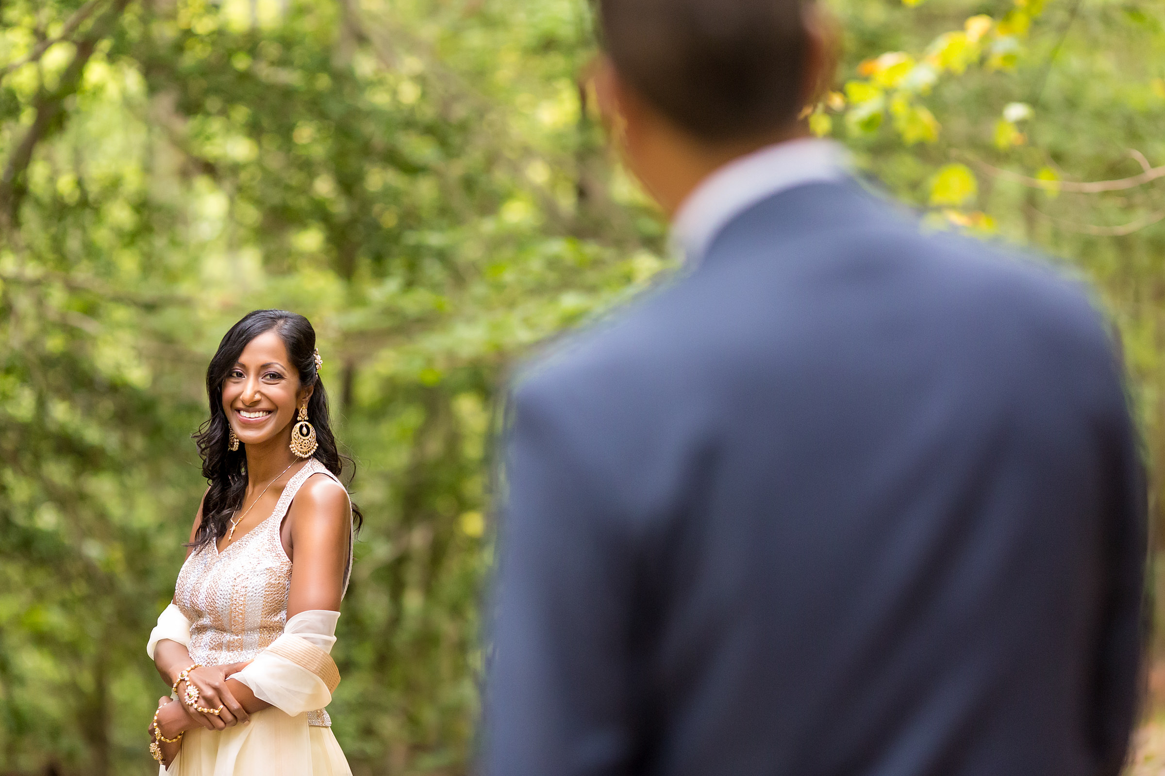 Bride against foliage with groom looking on - photo by Procopio Photography