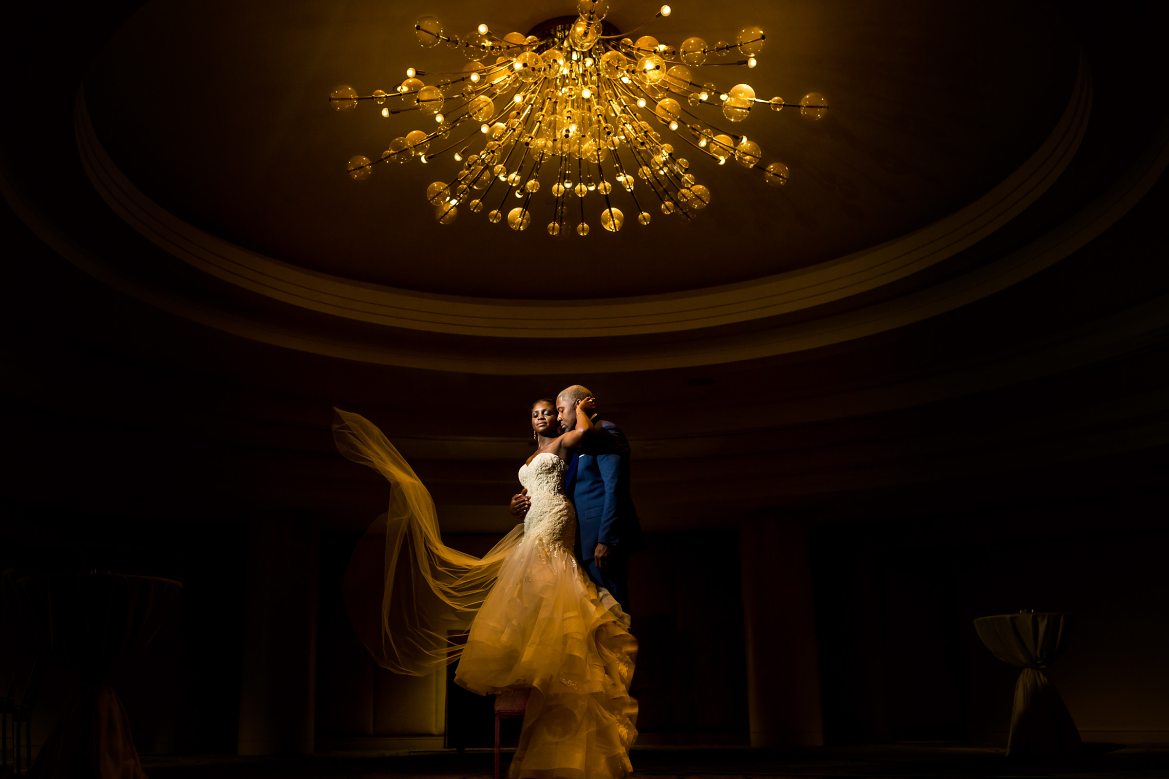 Bride and groom standing on chair under large chandelier - photo by Procopio Photography